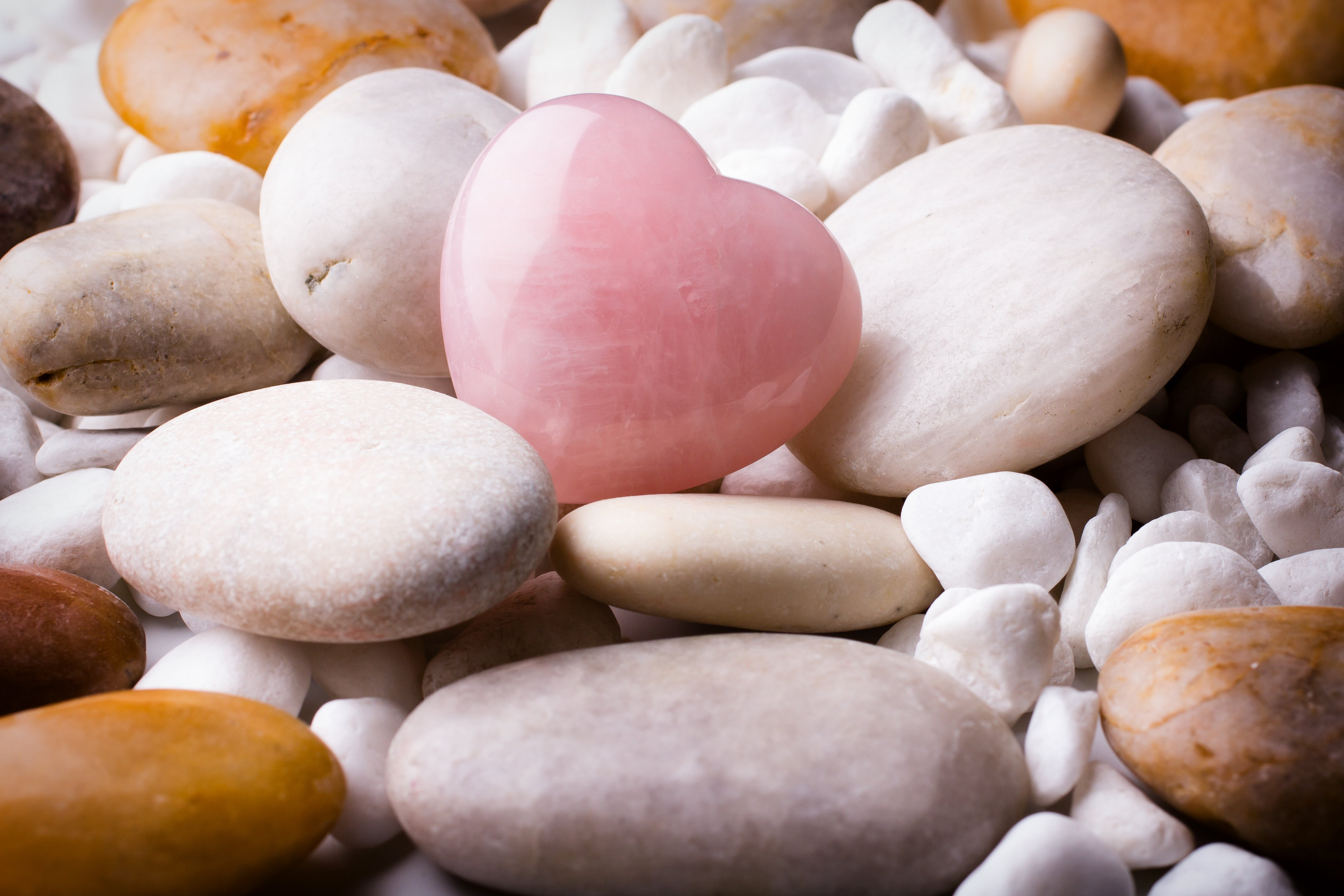 Pink heart stone on the spa stone background.