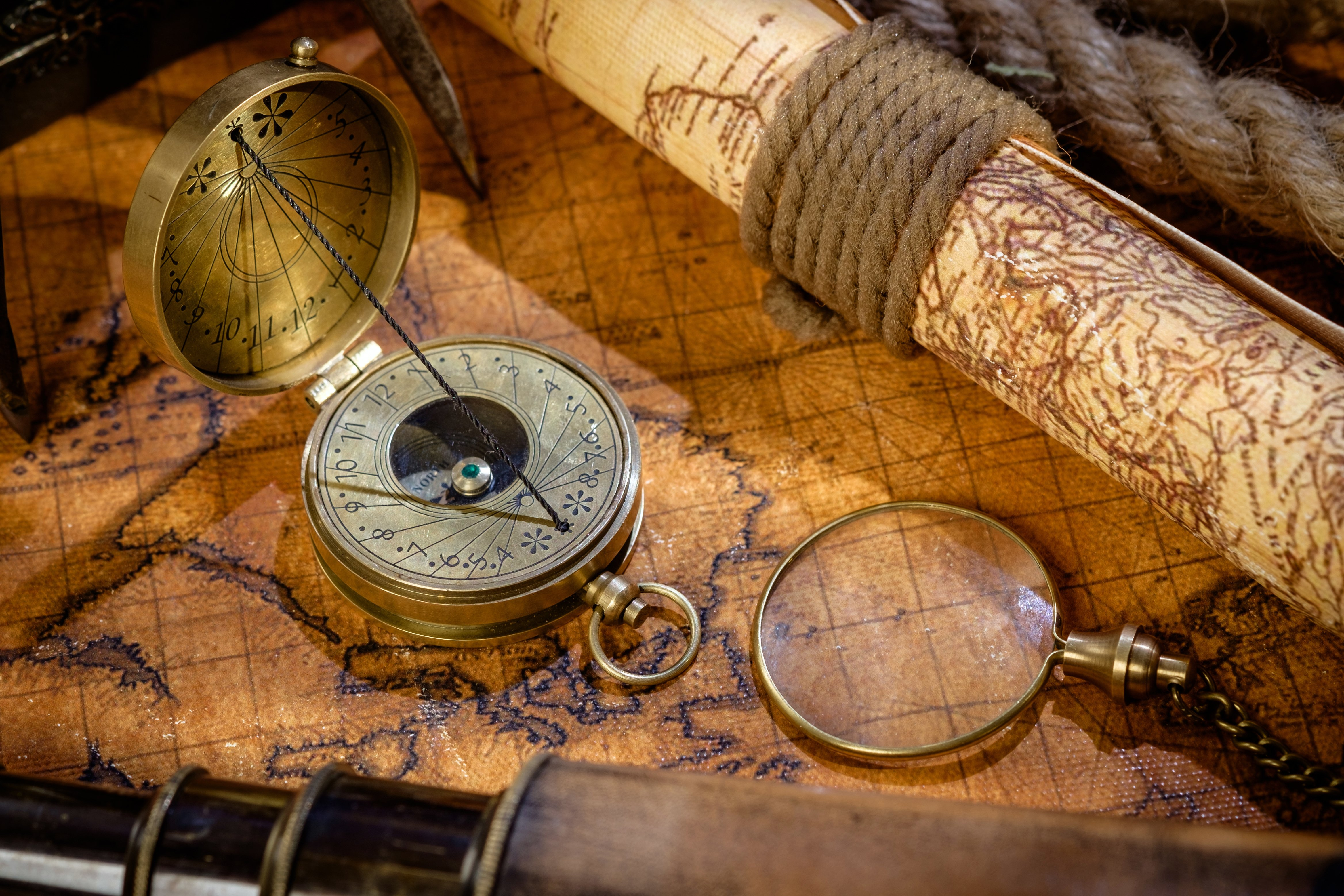 Old vintage retro compass, spyglass and magnifying glass on ancient world map. Vintage still life. Travel geography navigation concept background.