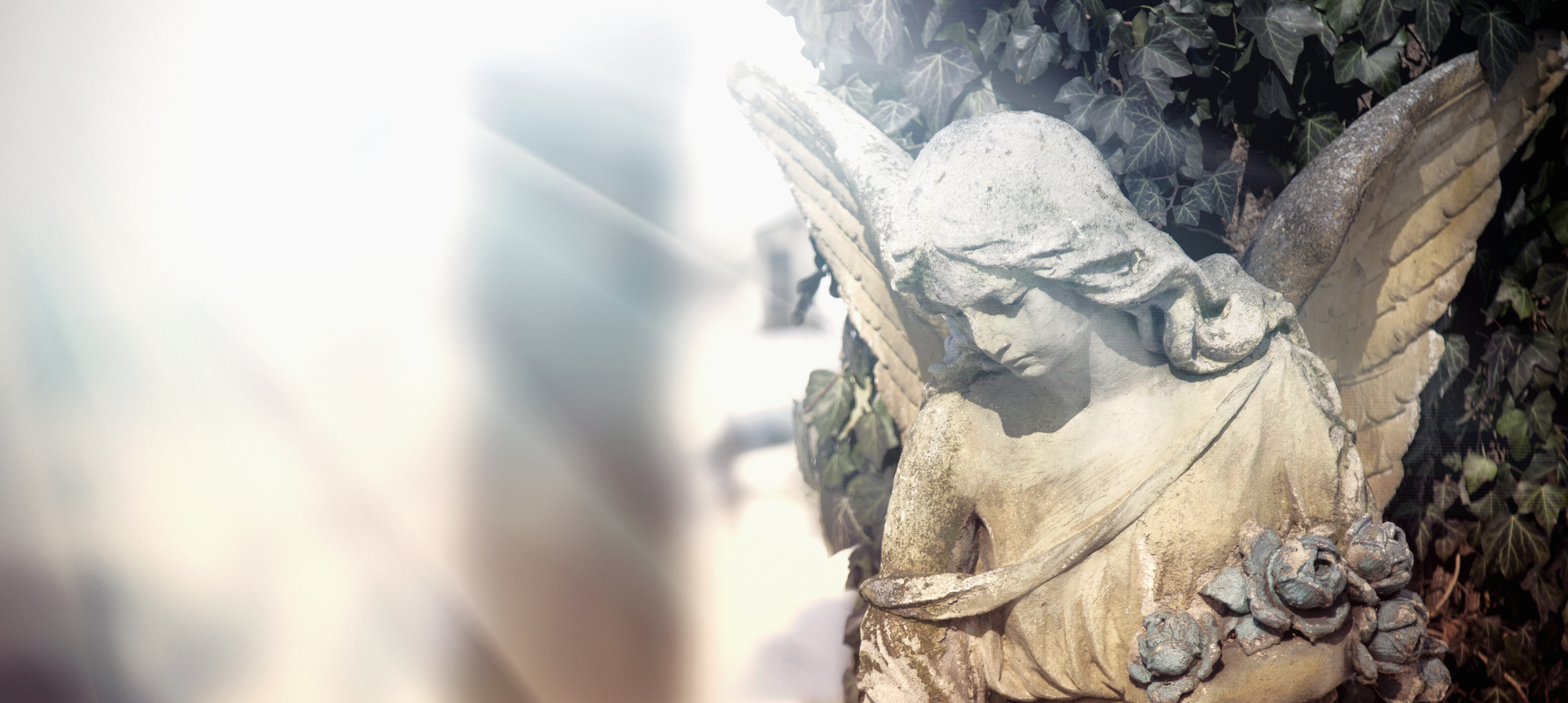 Vintage image of a sad angel on a cemetery. Ancient statue.