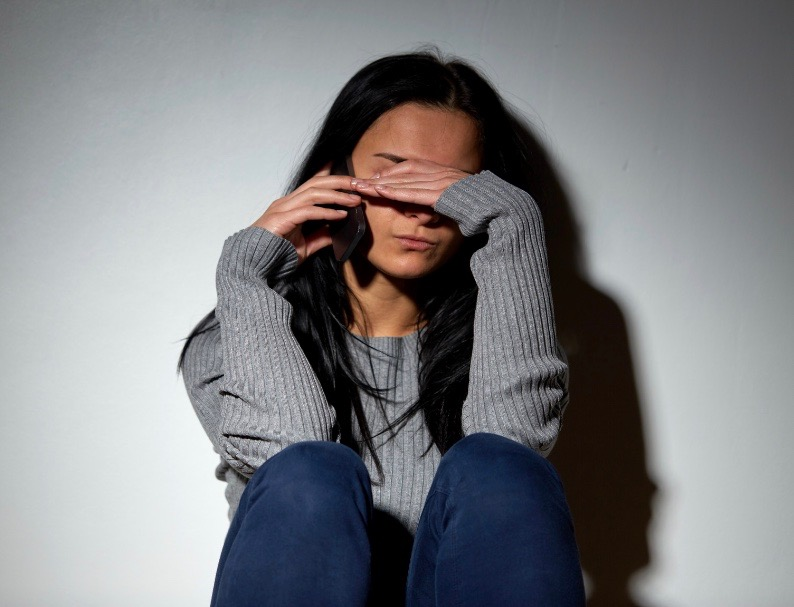 Unhappy woman covering her eyes in distress