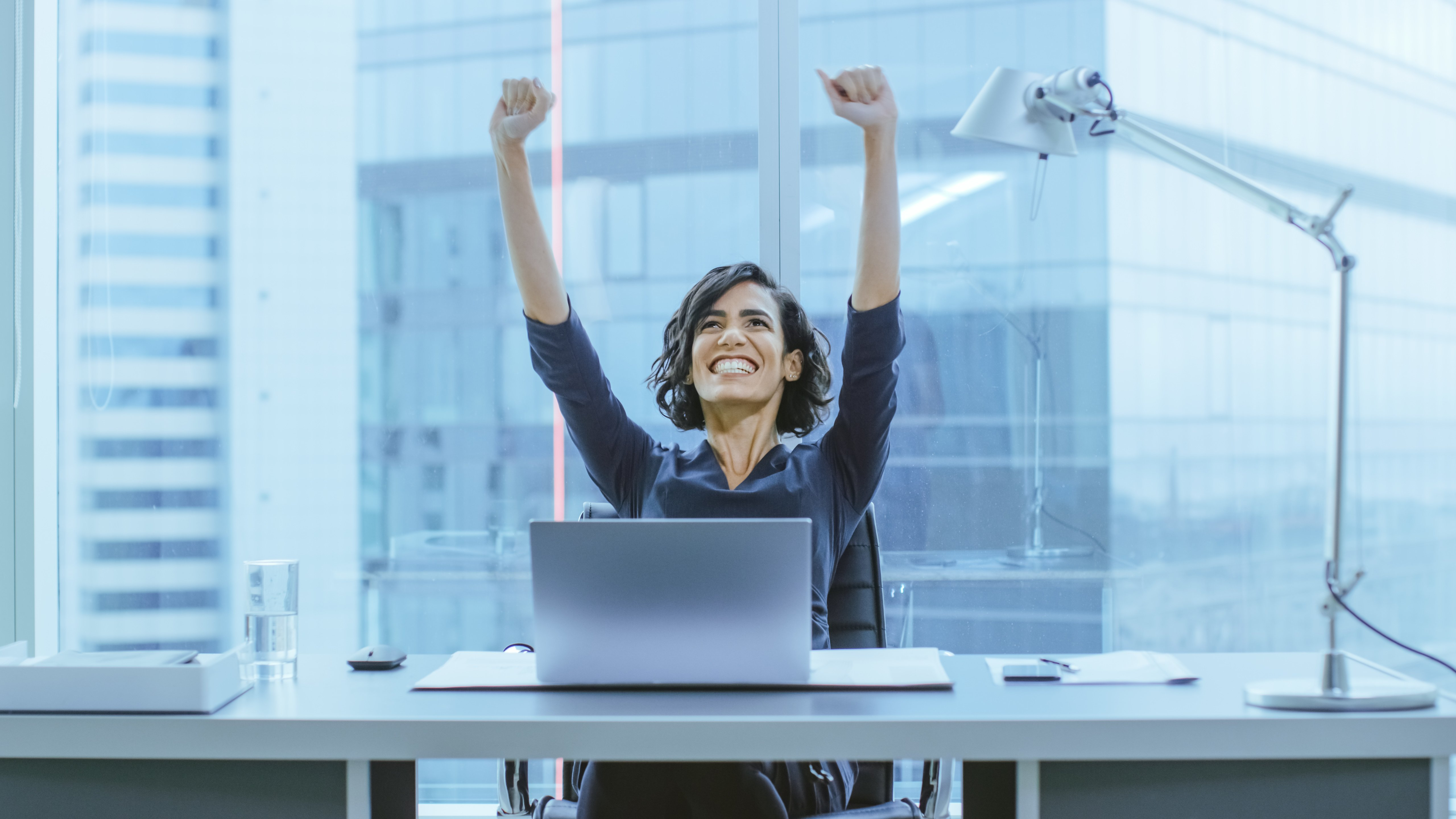 Shot of the Beautiful Businesswoman Sitting at Her Office Desk, Raising Her Arms in a Celebration of a Successful Job Promotion.