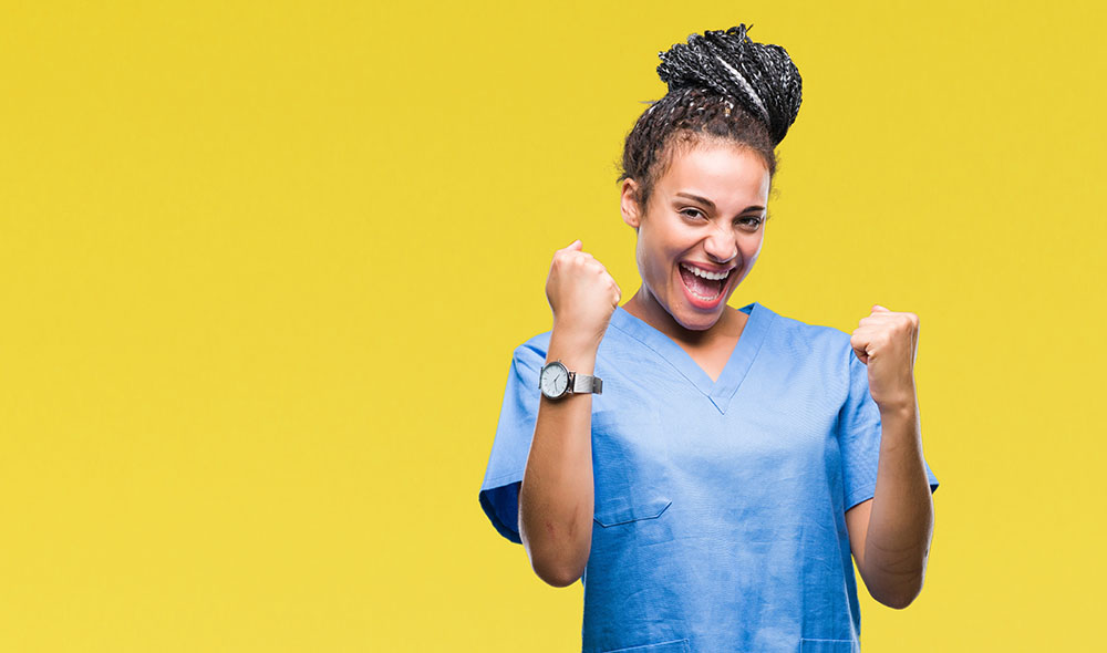Young braided hair african american girl professional nurse over isolated background very happy and excited doing winner gesture with arms raised, smiling and screaming for success. Celebration concept.