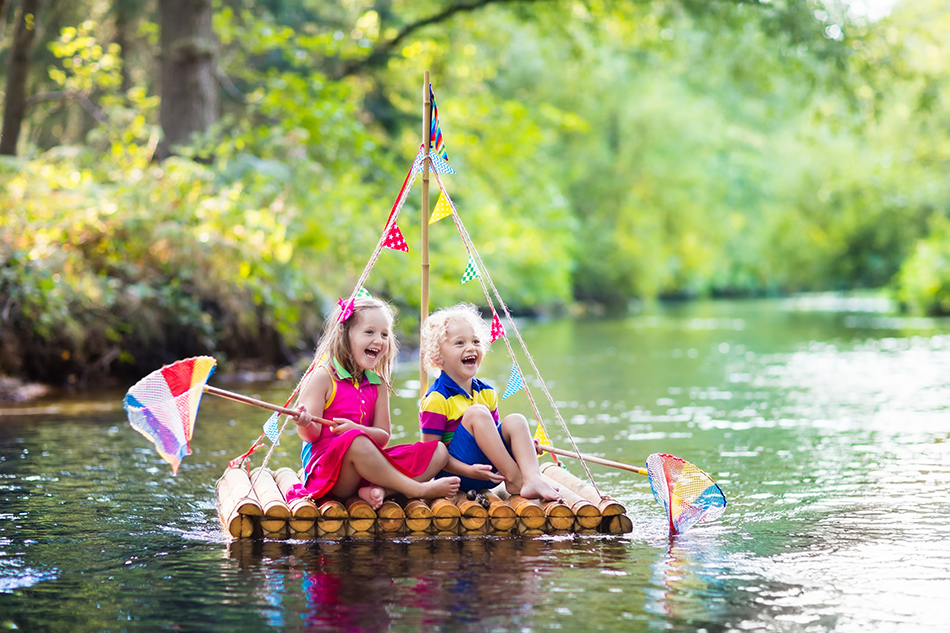 Two children on wooden raft catching fish with a colorful net in a river and playing with water on hot summer day. Outdoor fun and adventure for kids. Boy and girl in toy boat. Sailor role game.