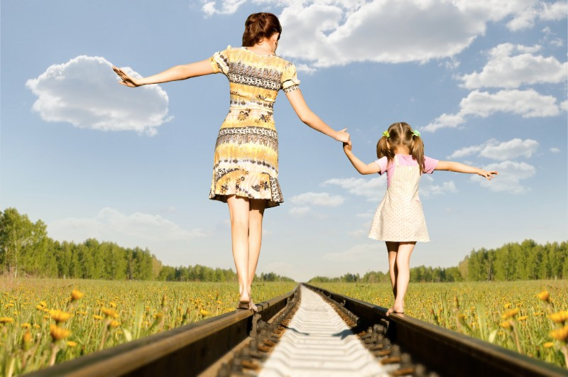 mother adn child walking along train tracks