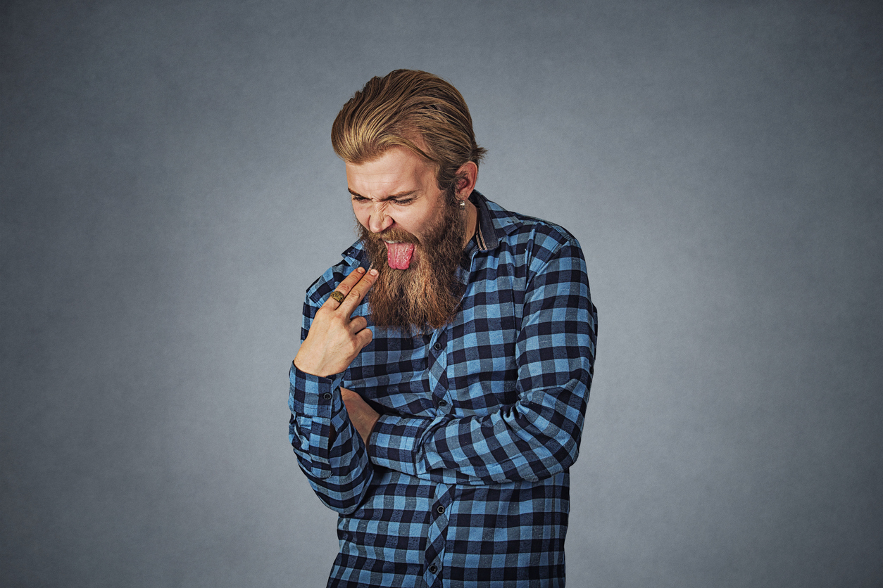 Disgusted man with finger in mouth displeased wants to throw up. Hipster male with beard in blue plaid checkered shirt  Isolated on gray grey studio Background. Negative face expression, human emotion