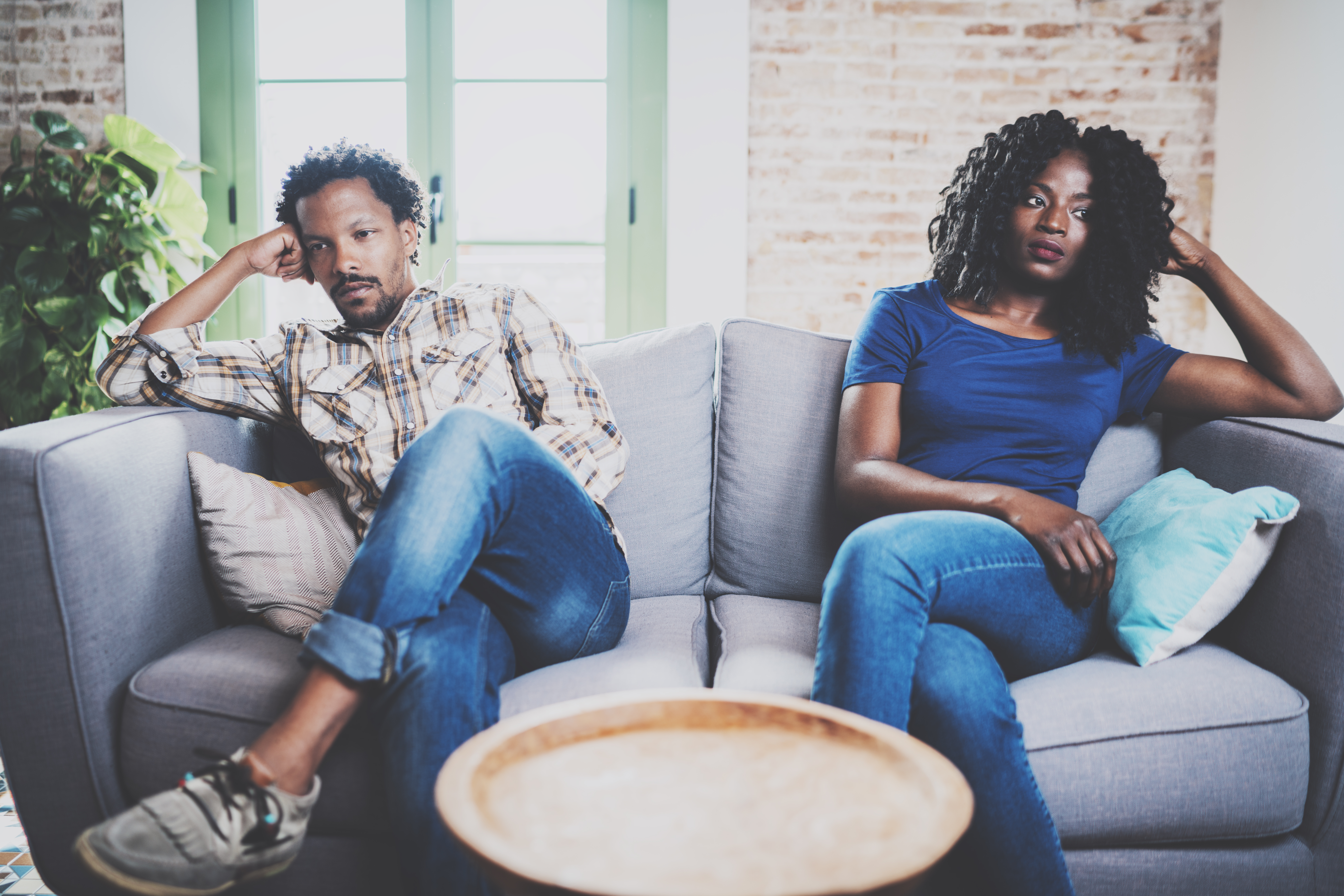 couple sitting on a sofa turned away from one another