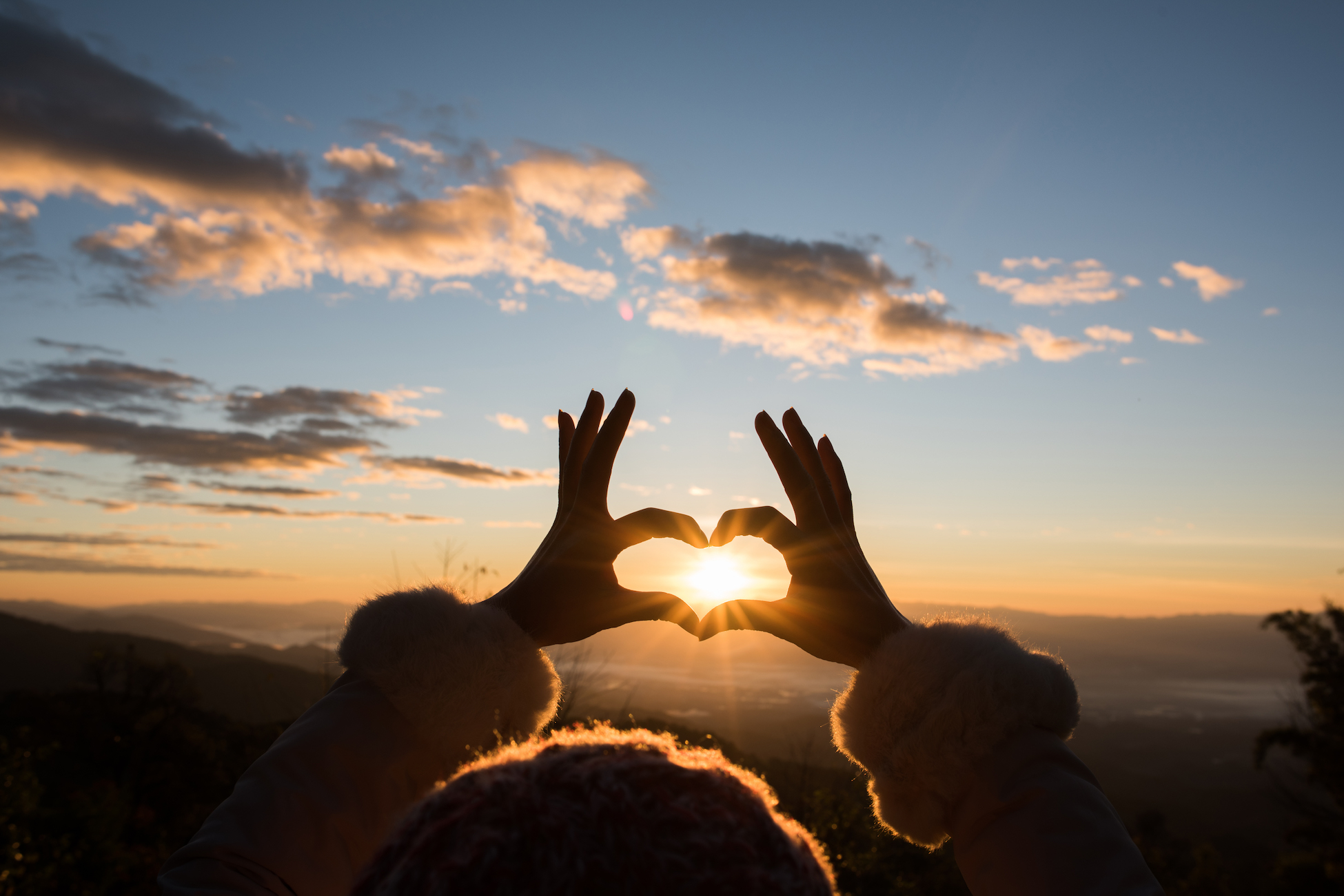 Silhouette hands forming a heart shape with sunrise