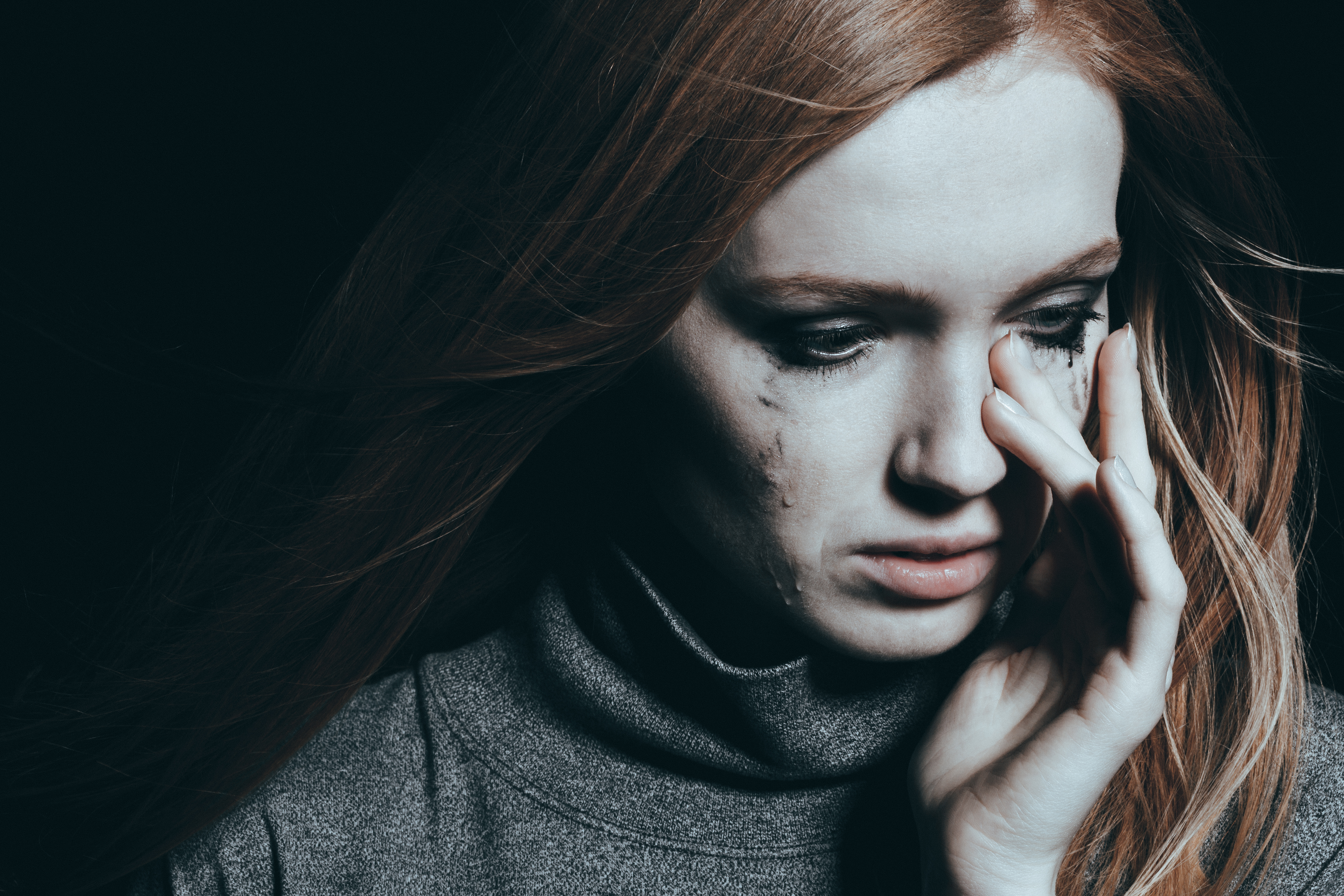 Beautiful, young woman covering her tears, black background