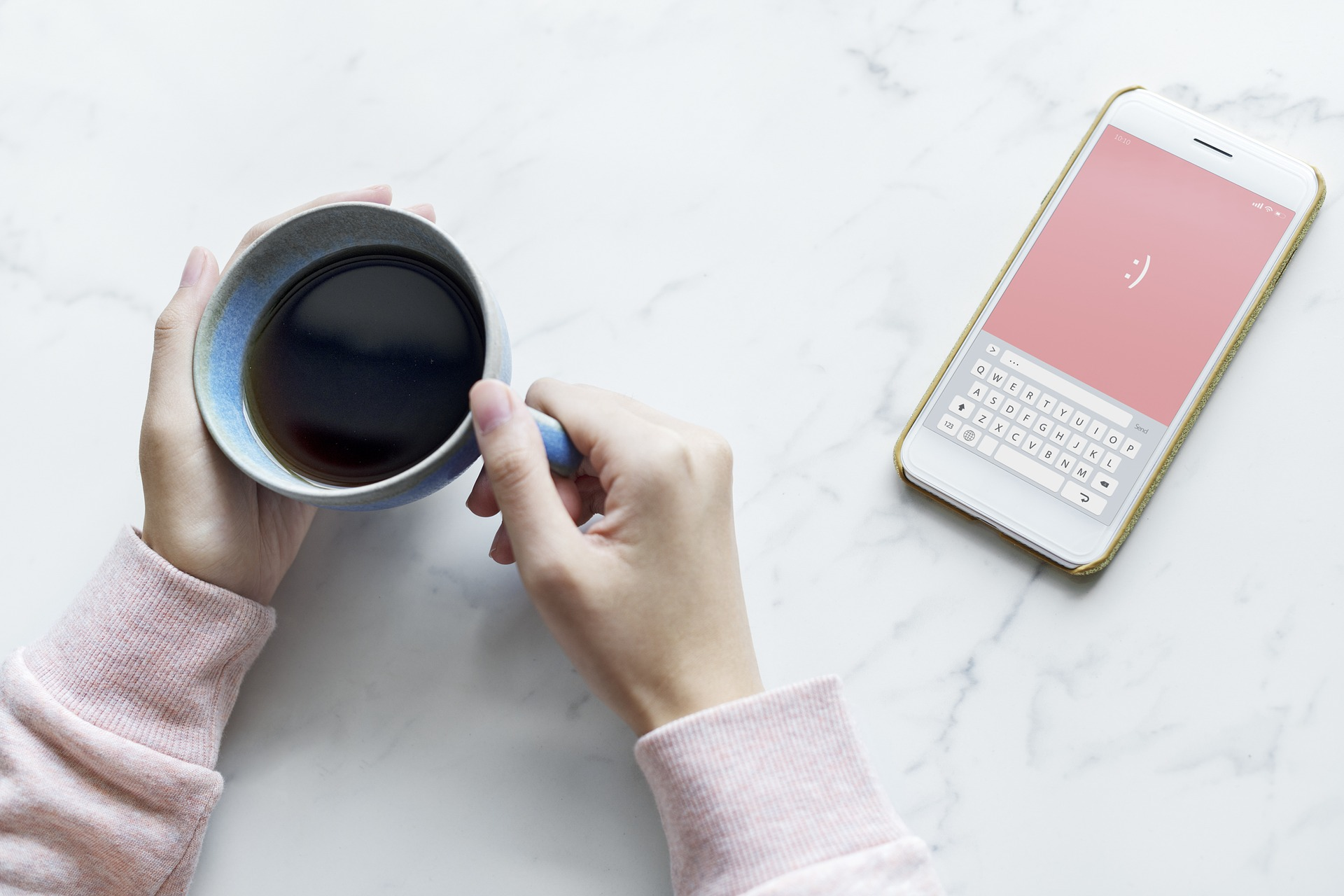 girl holding cup of coffee with phone on the table