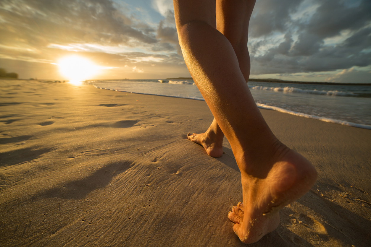 Young woman walking on a beach making foot print on the sand. Sun setting on the sea.