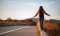 Beautiful woman walking and balancing on street curb or curbstone during sunset with copy space