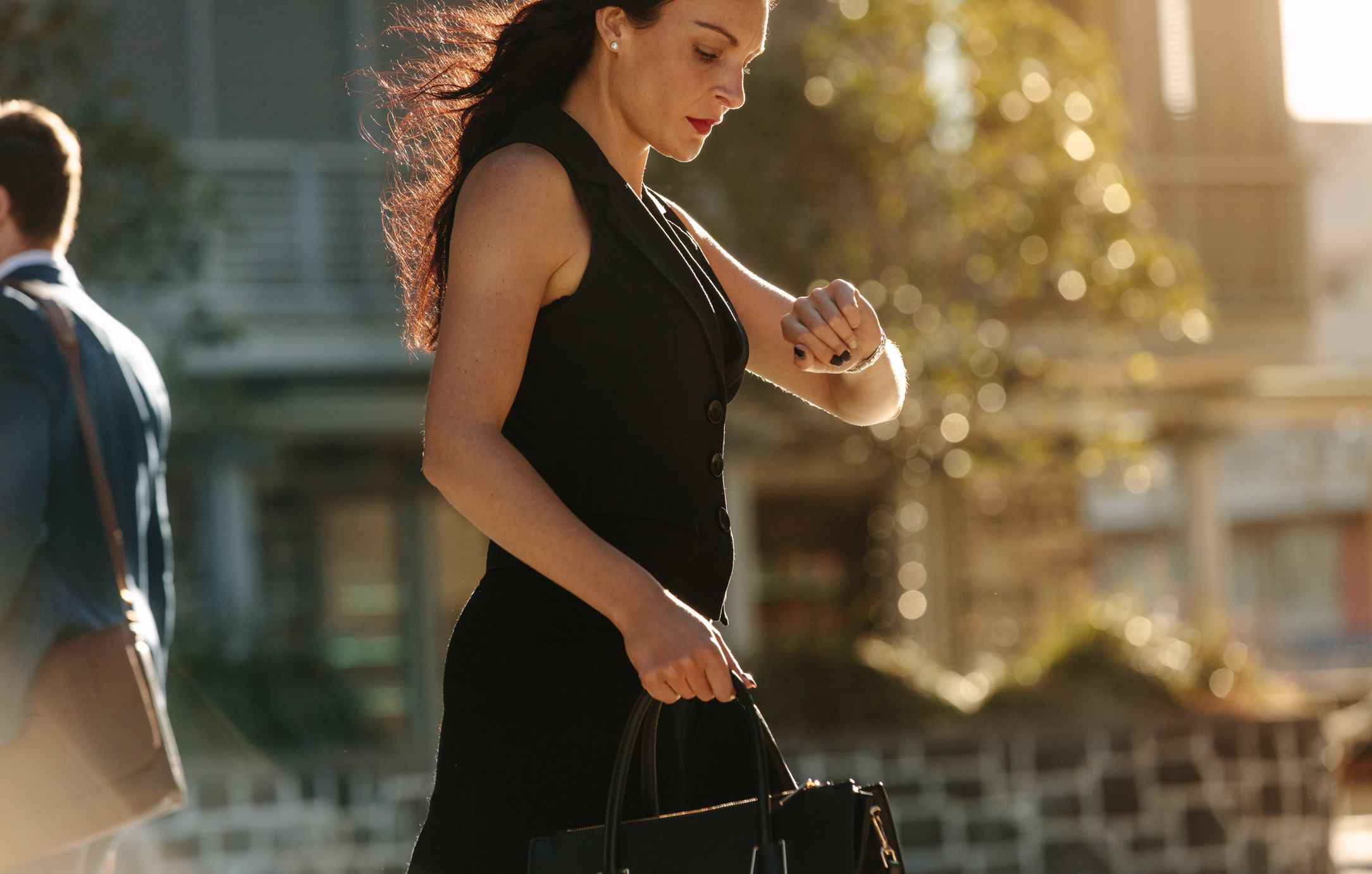 Woman looking at her wrist watch while commuting to office in the morning carrying her bag. Office going people walking on a street in the morning.