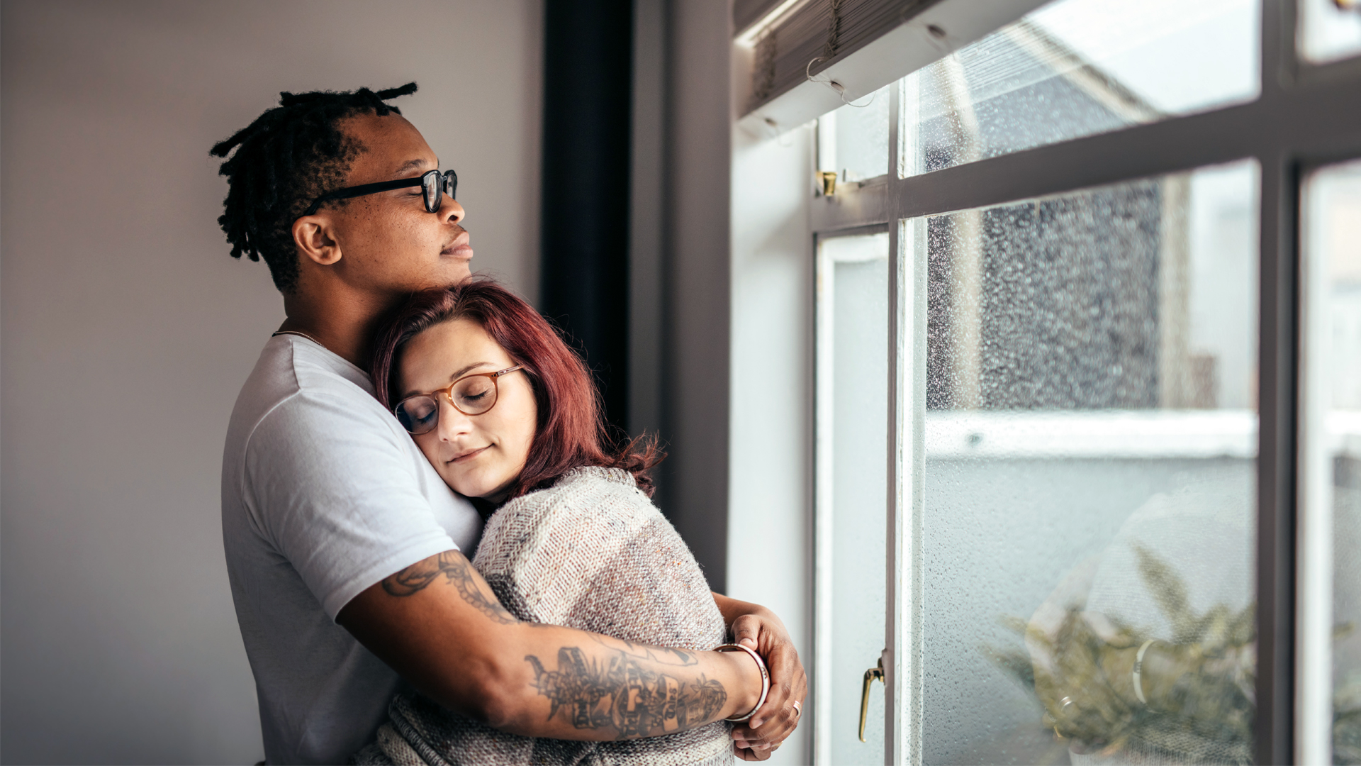 Interracial couple hugging near window