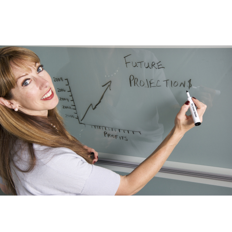 woman with white shirt writing on a white board looking at the camera