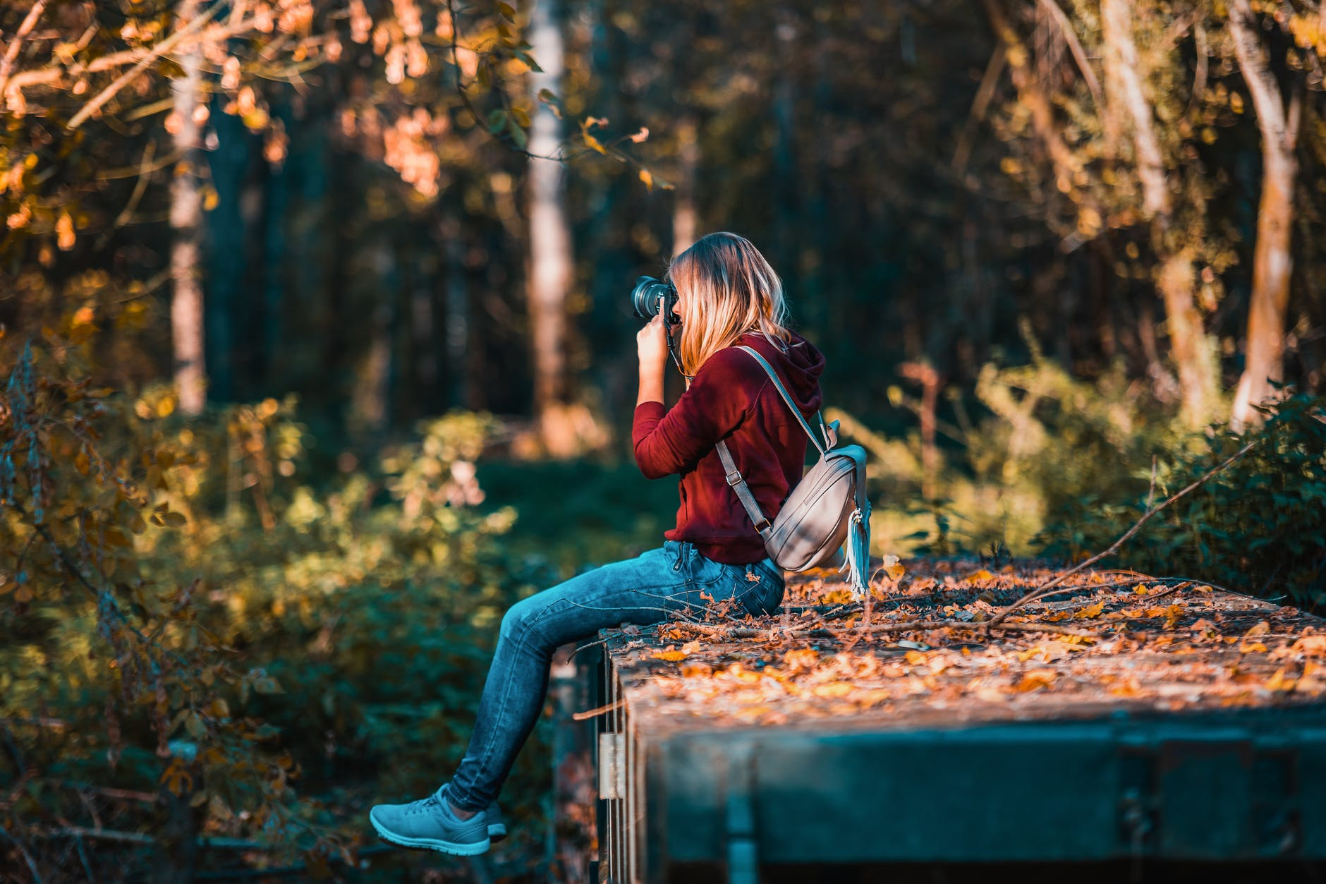 A woman sitting in the woods taking a photo with her camera