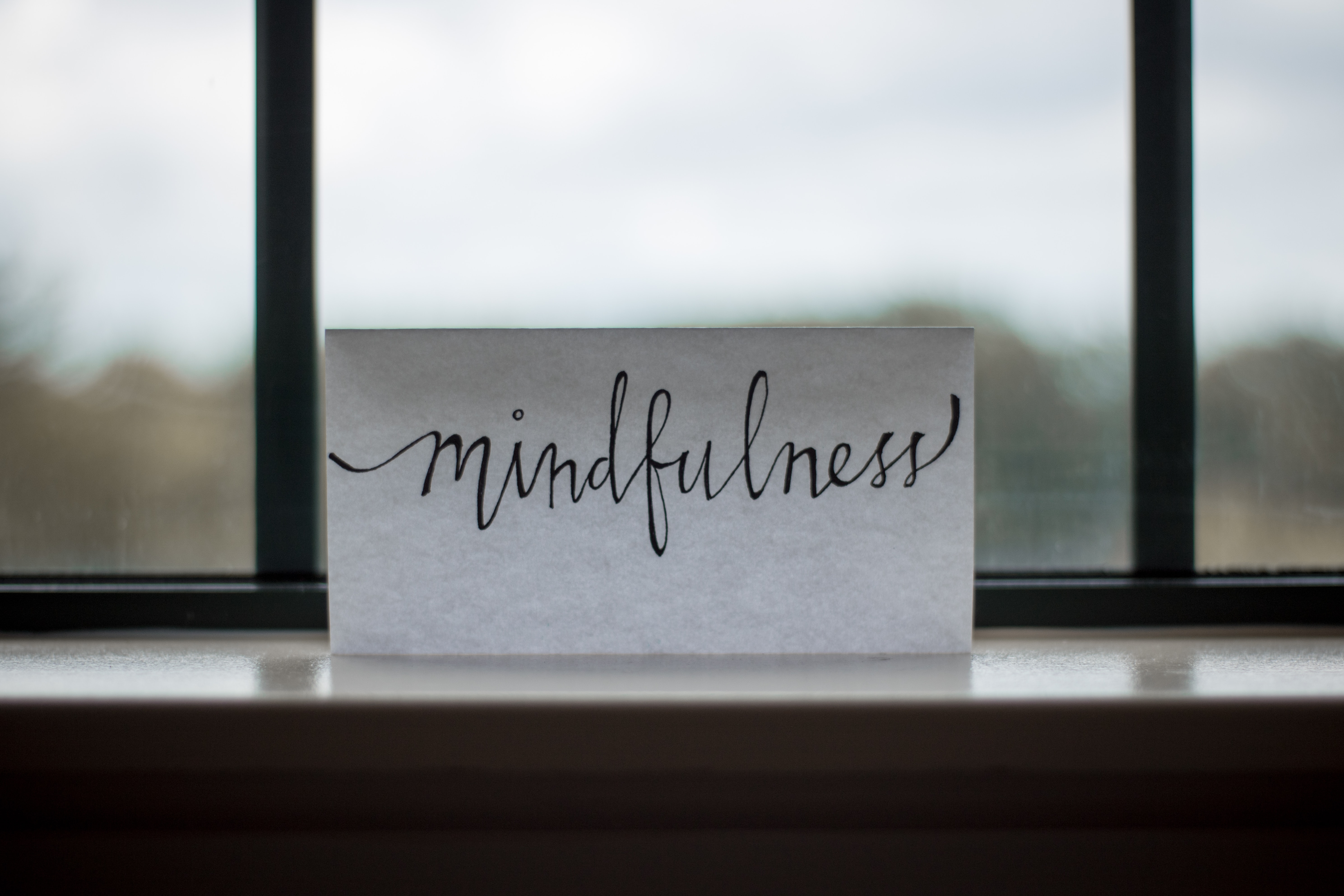 """Mindfulness"" wrritten on white paper, standing on the window ledge"