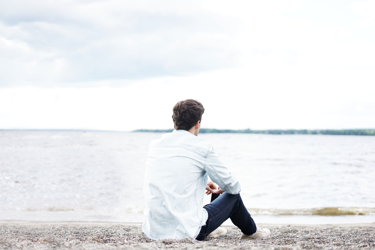 A man sitting and thinking in front of a bay