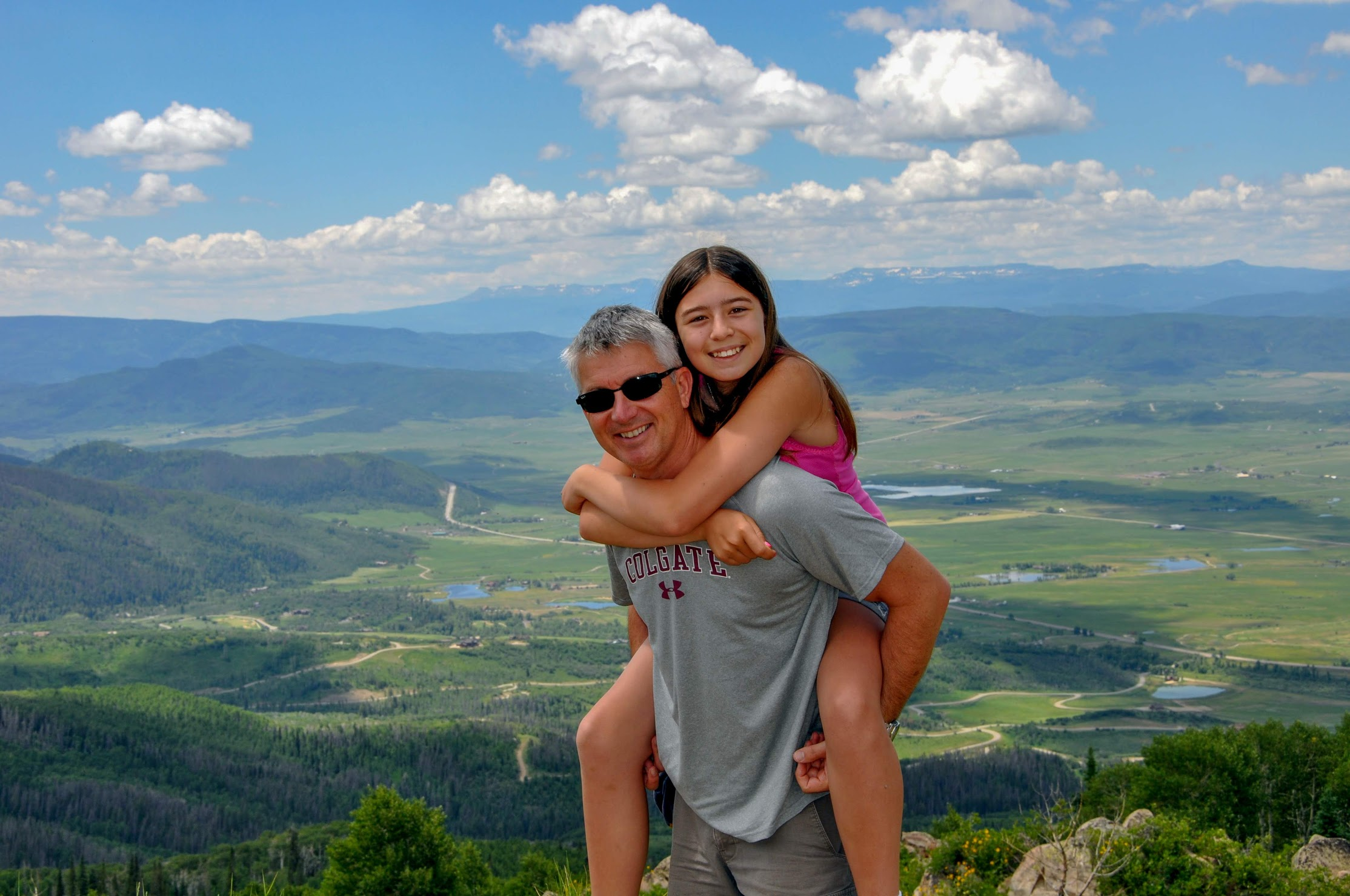 dad carrying daughter on piggyback on a mountain