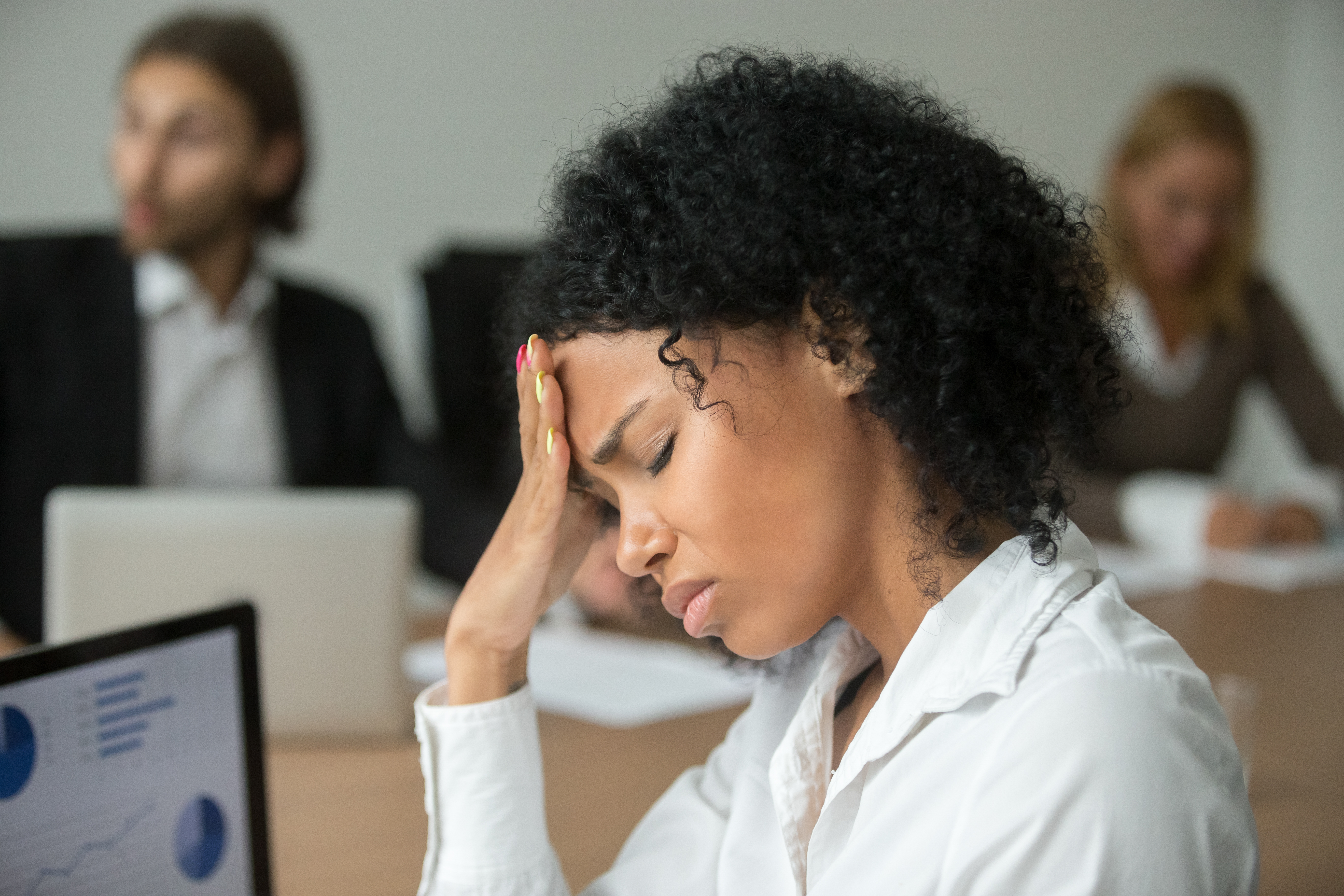 Woman feeling stressed and burnt out at work.
