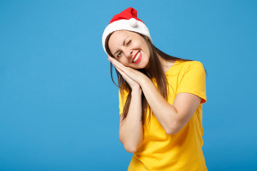 A woman in a bright yellow shirt and red Santa hat places her head against her hands, indicating sleepiness.; all against blue background