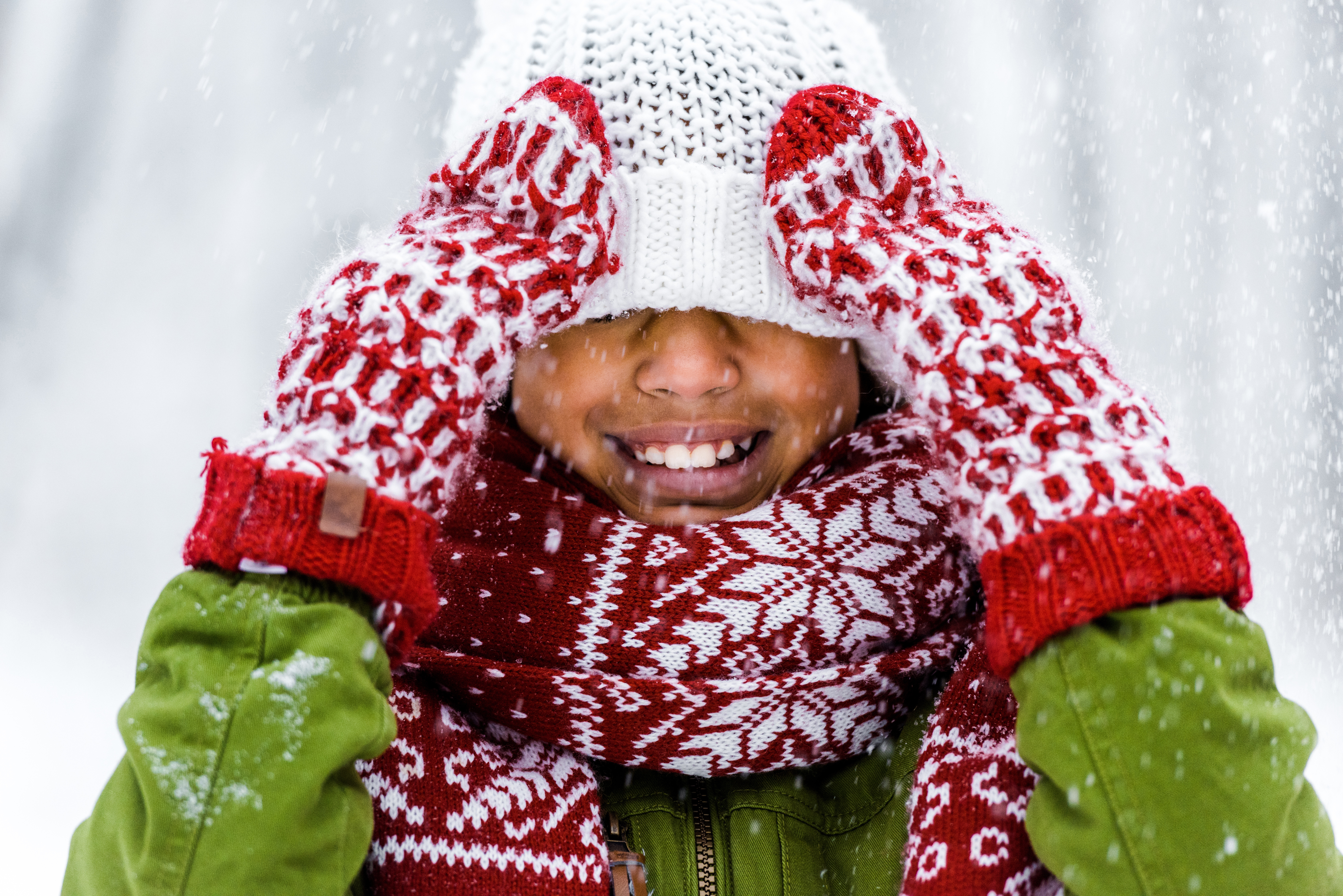 Cute African American child with knitted hat pulled over eyes smiling during snowfall