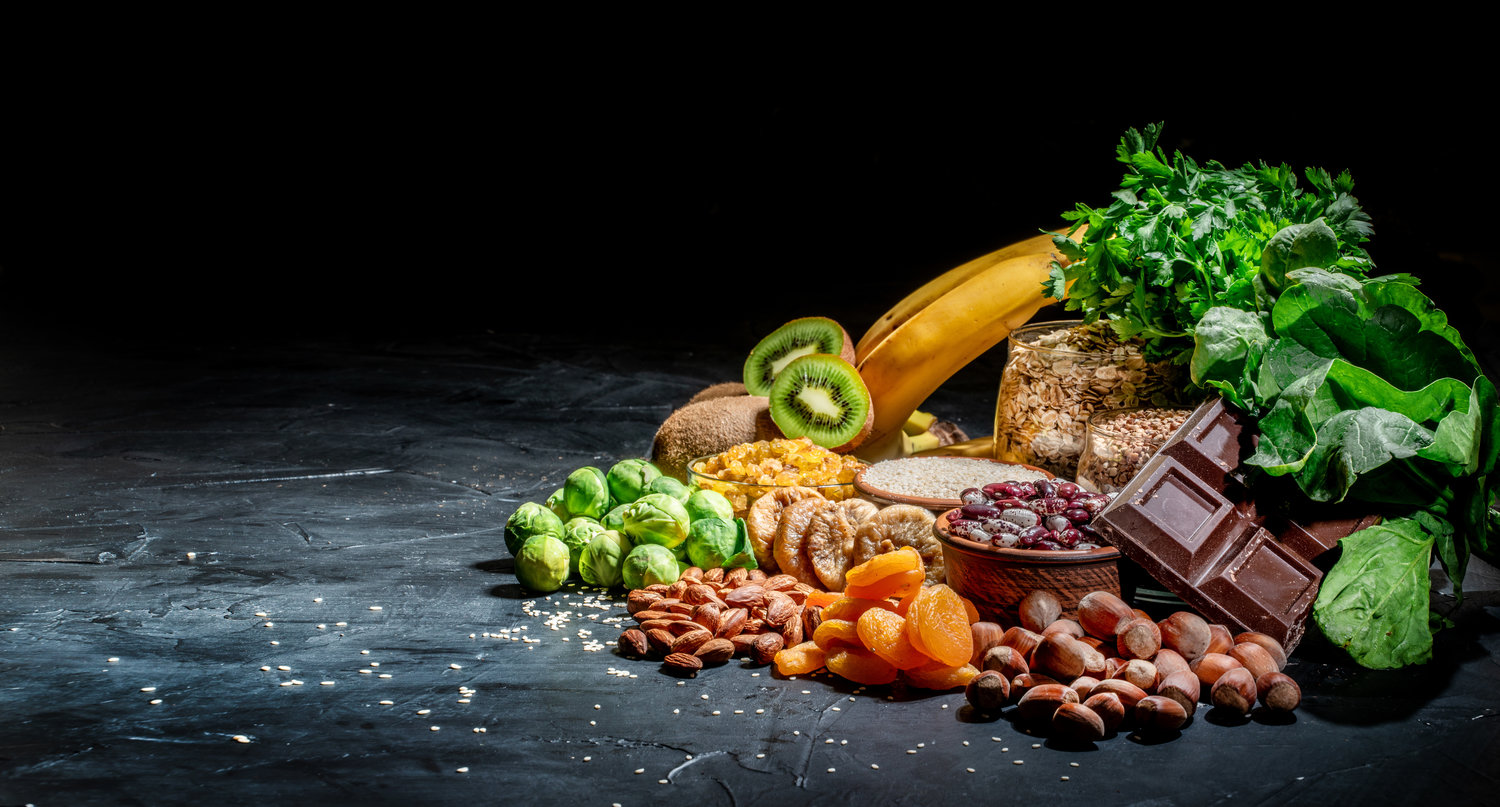 Assortment of high magnesium sources: bananas, nuts, oatmeal, buckwheat, peanuts, spinach chard, dark chocolate and sesame seeds on dark background