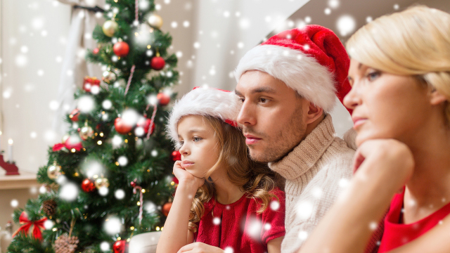 christmas, holidays, sadness and people concept - sad family in santa helper hats with gift boxes at home