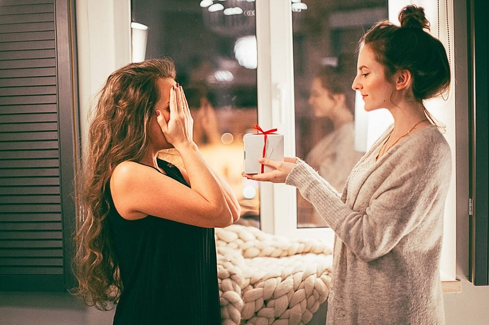 woman at home offering gift to a surprised girlfriend