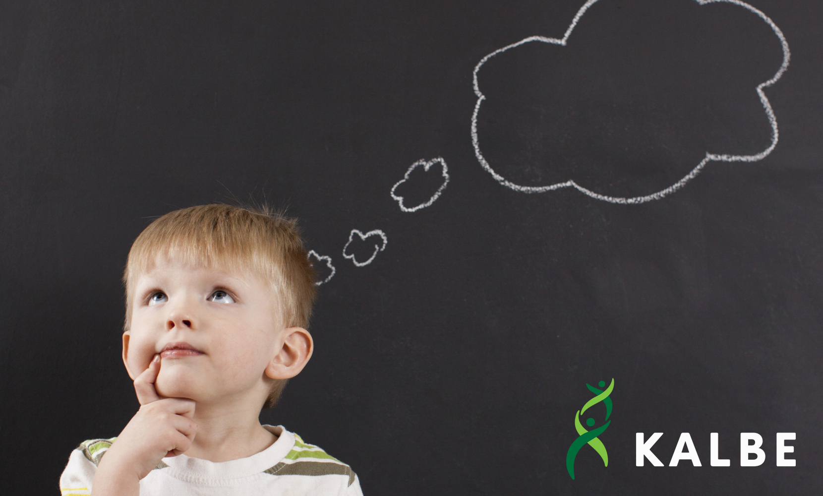 Cute toddler boy (2-3) standing against blackboard with thought bubble written in chalk