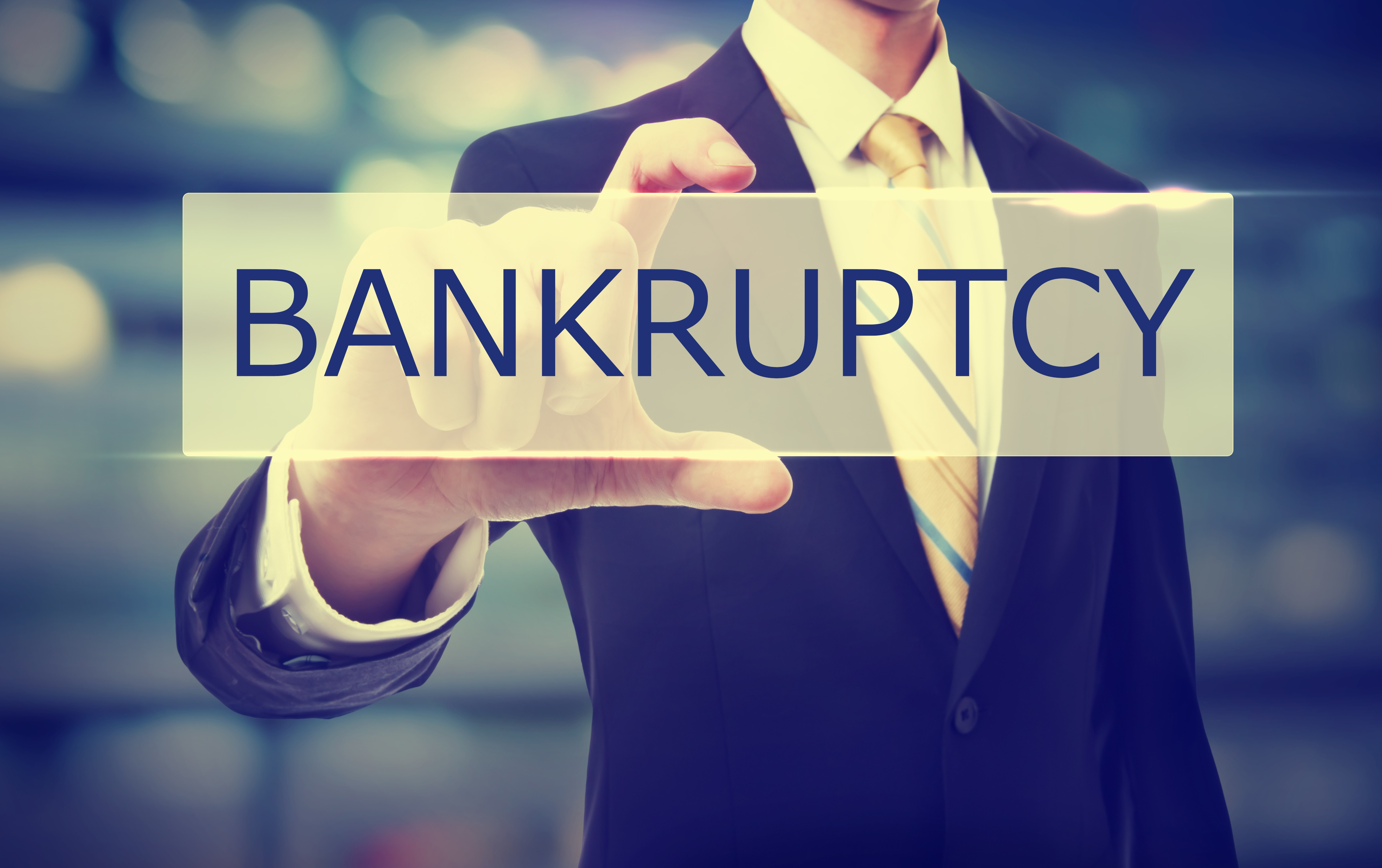 Business man holding Bankruptcy on blurred abstract background