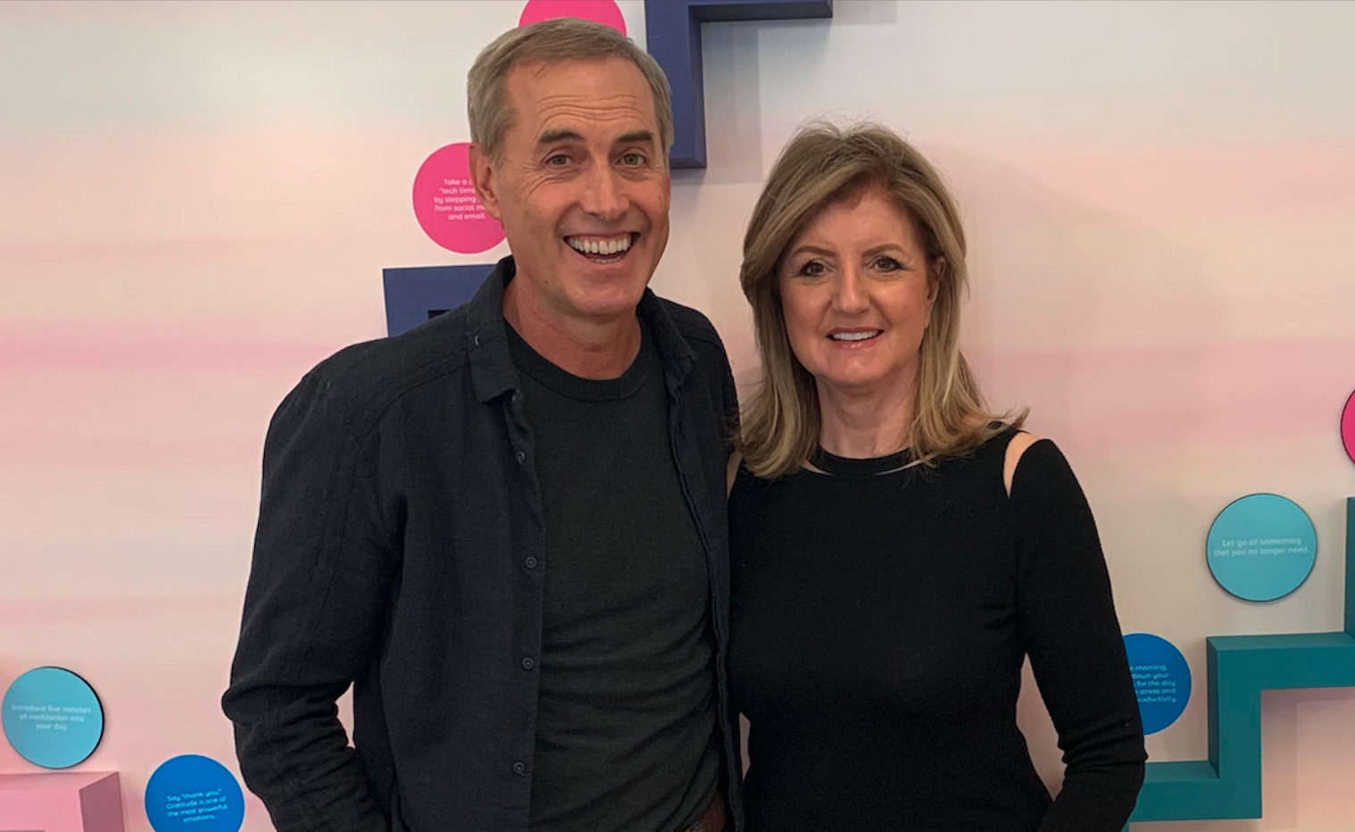 B.J. Fogg and Arianna Huffington in front of Thrive's Microstep Wall.