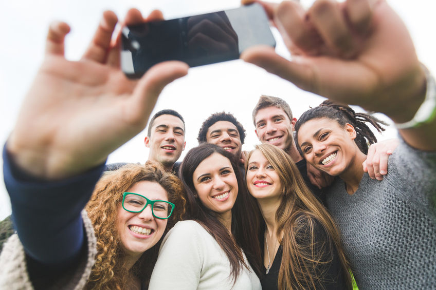 34188632 - multiethnic group of friends taking selfie at park