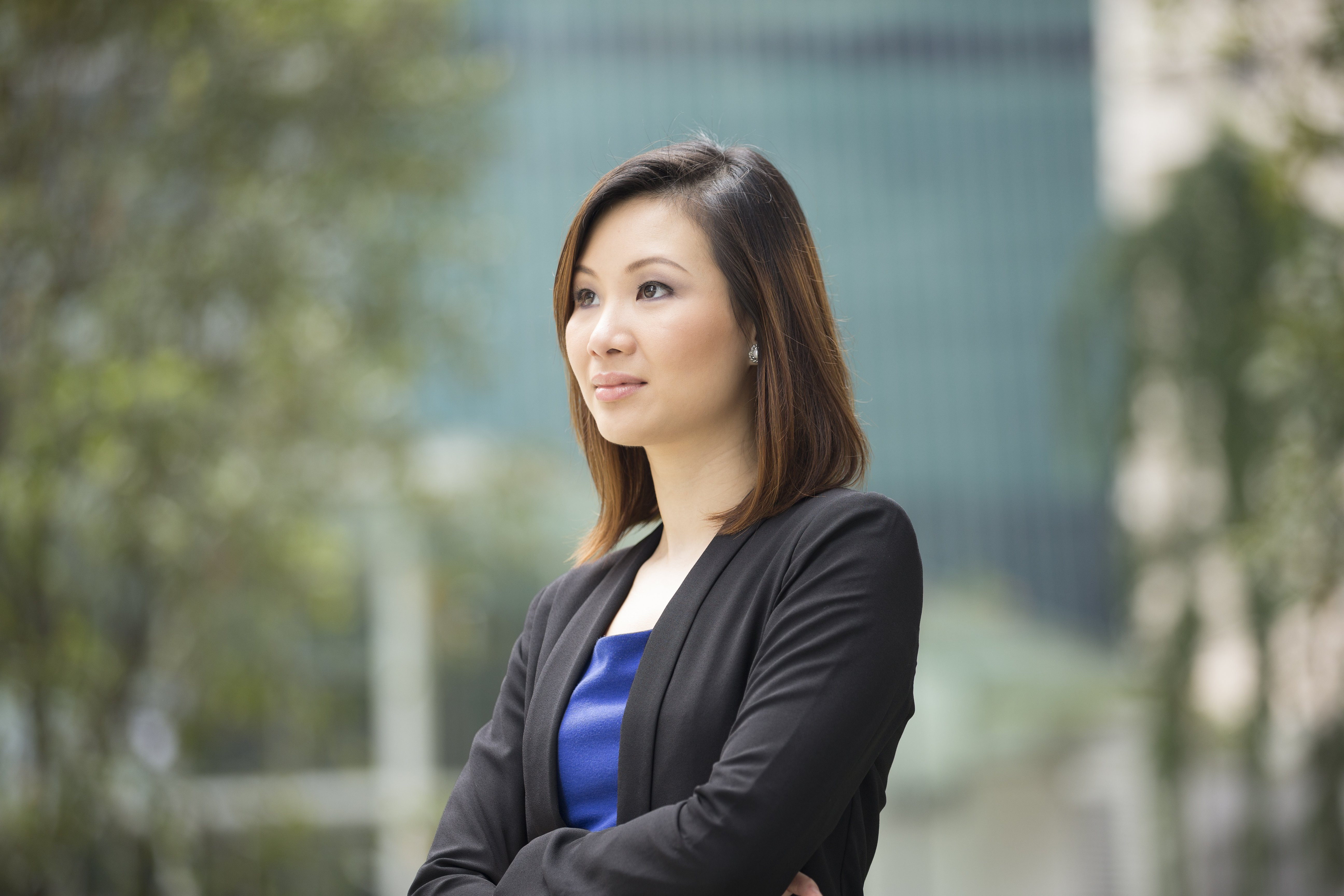 Portrait of thoughtful Chinese businesswoman looking away. Asian business woman in smart business suitstanding outside in modern city.