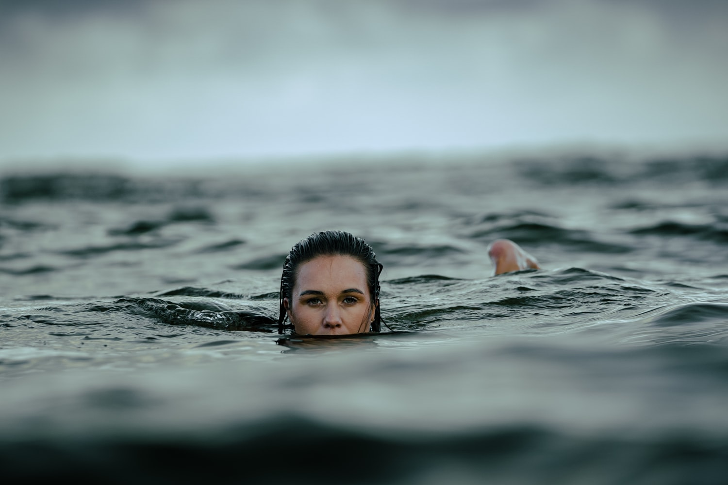 A woman's face trying to stay afloat in the middle of the ocean