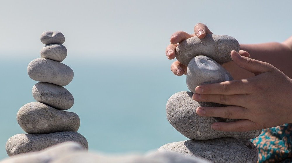 Hands Patiently Stacking Stones
