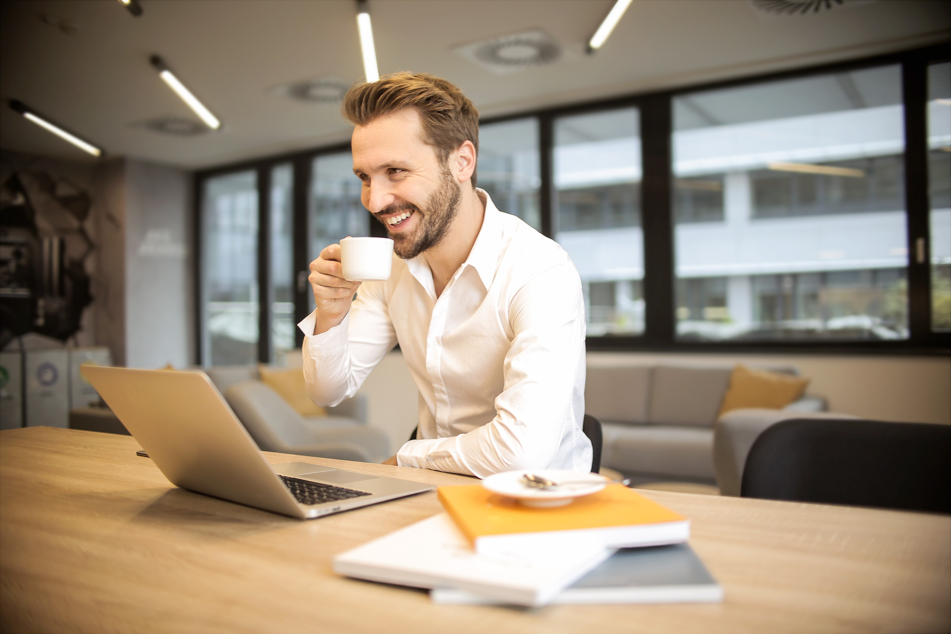 Man drinking coffee and smiling while looking at his computer