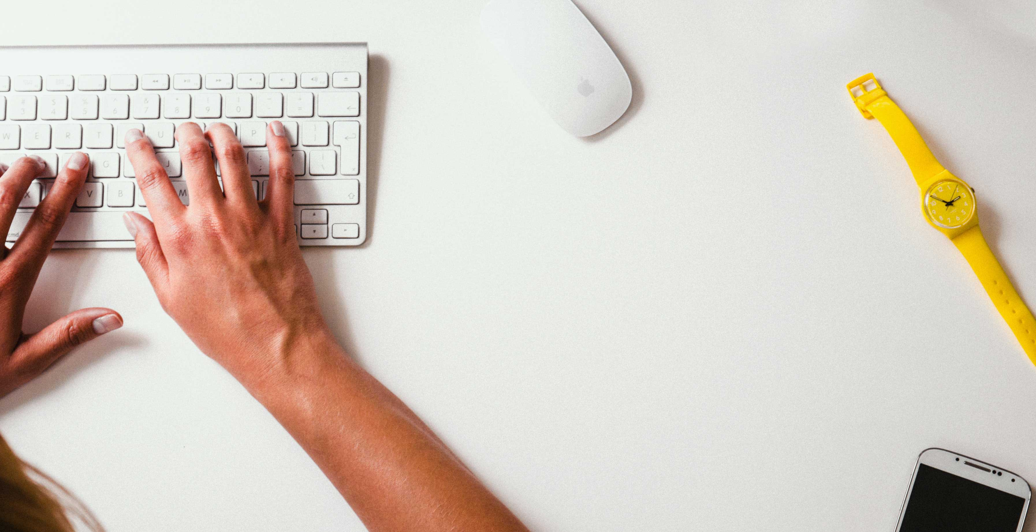 How to Avoid Burnout with a Freelance Side Hustle || a white desk with a yellow watch and someone typing on a keyboard