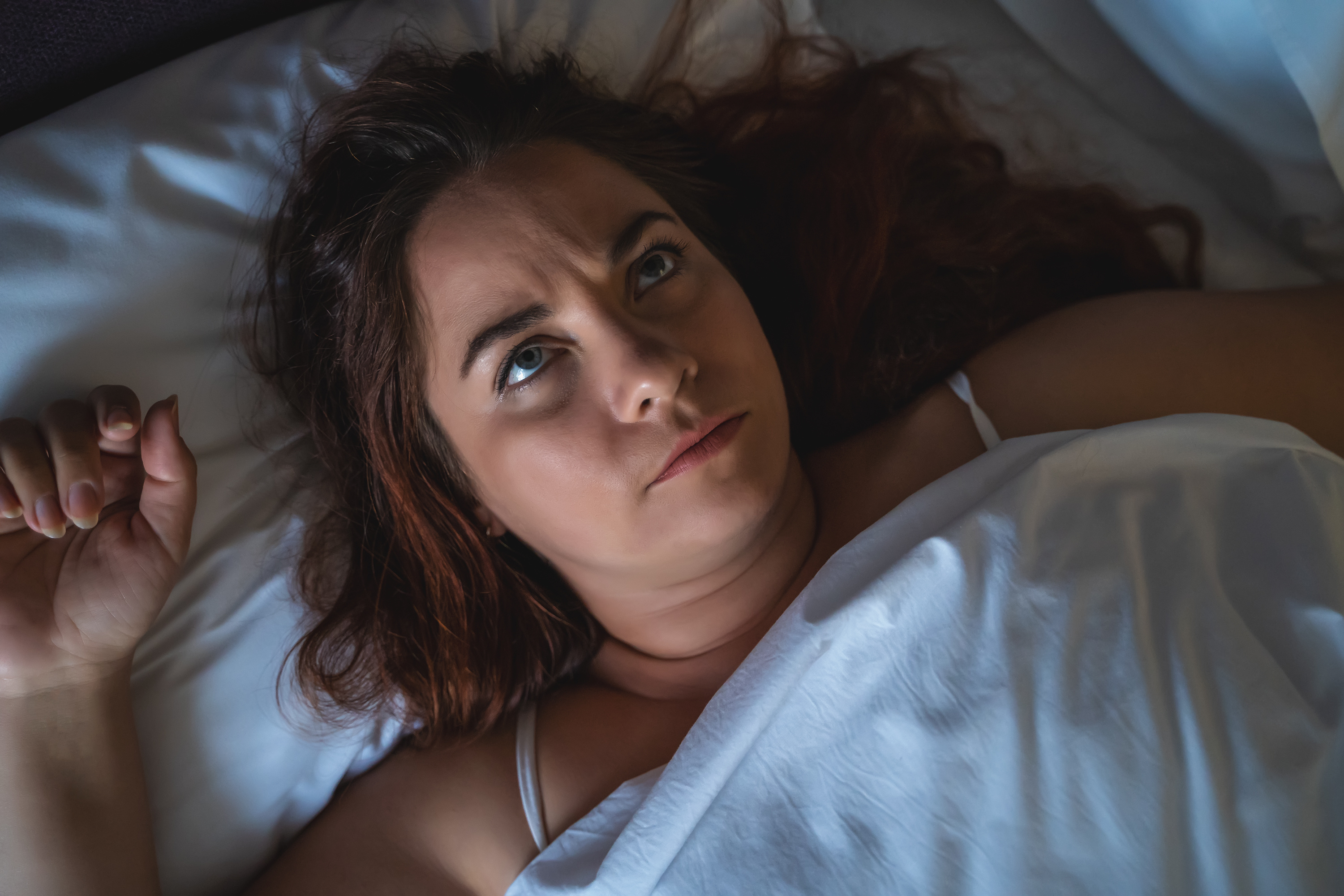 Young stressed or depressed woman lies in bed, can not sleep. Insomnia concept, top view.