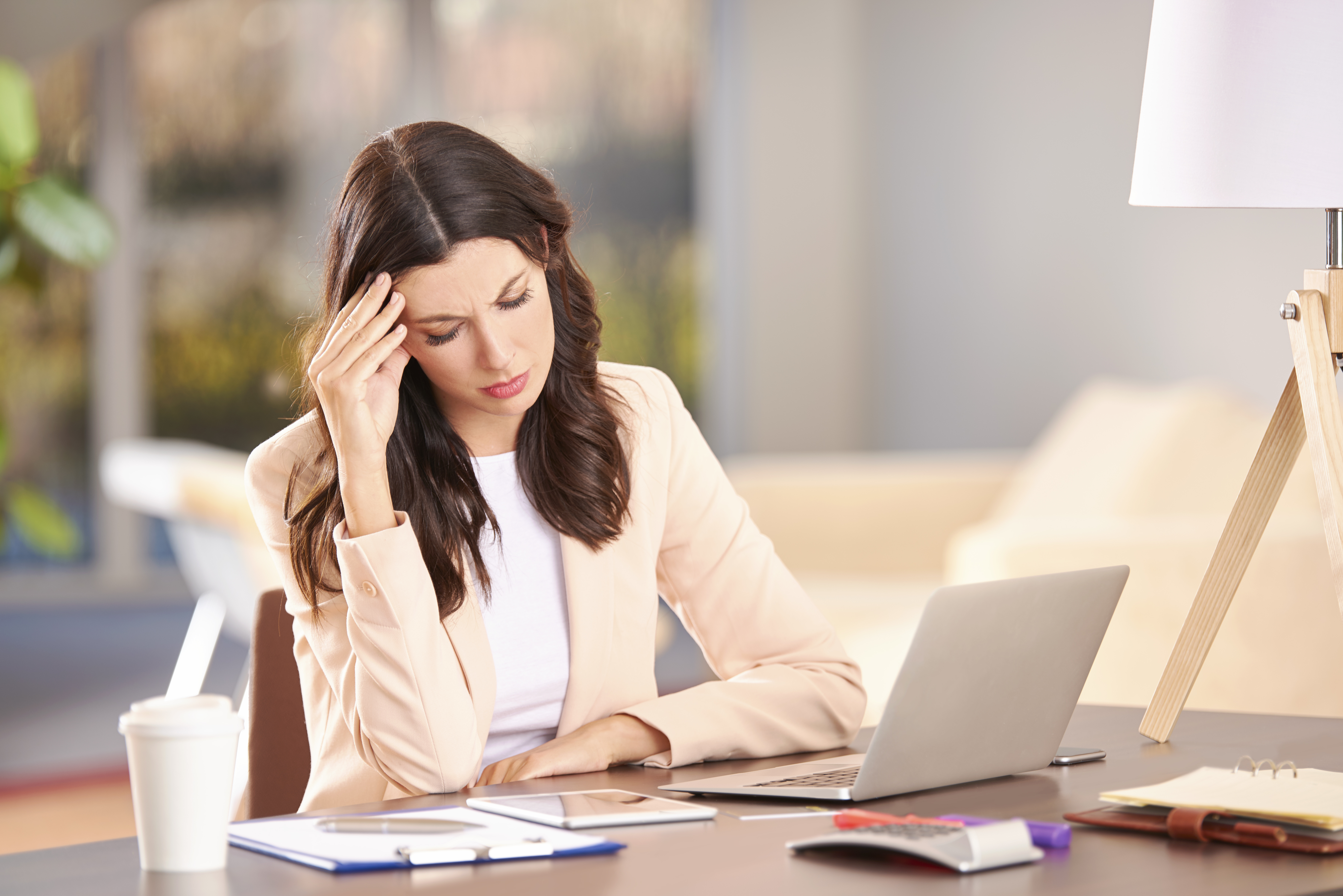 Shot of a CEO businesswoman looking stressed while sitting in her office in front of laptop.