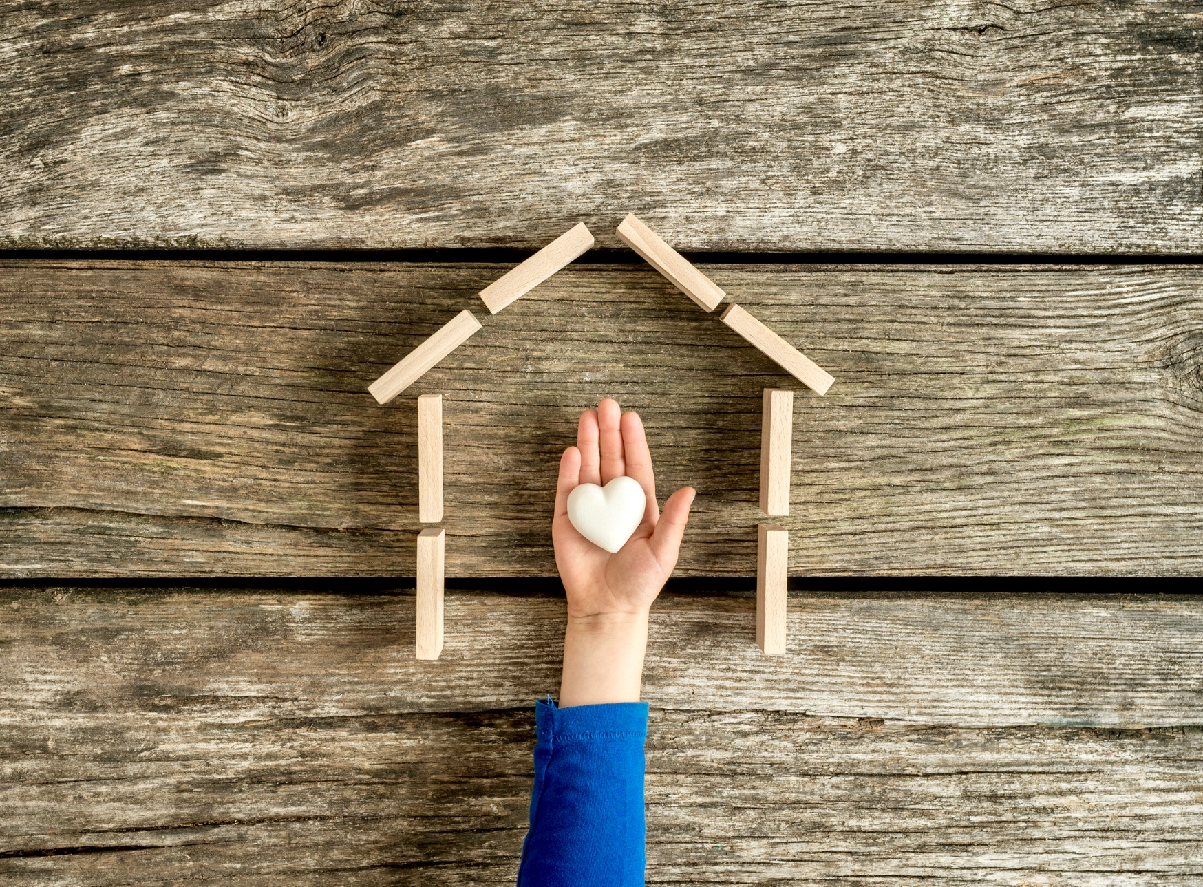 Child's hand holding a heart within the frame of a house.