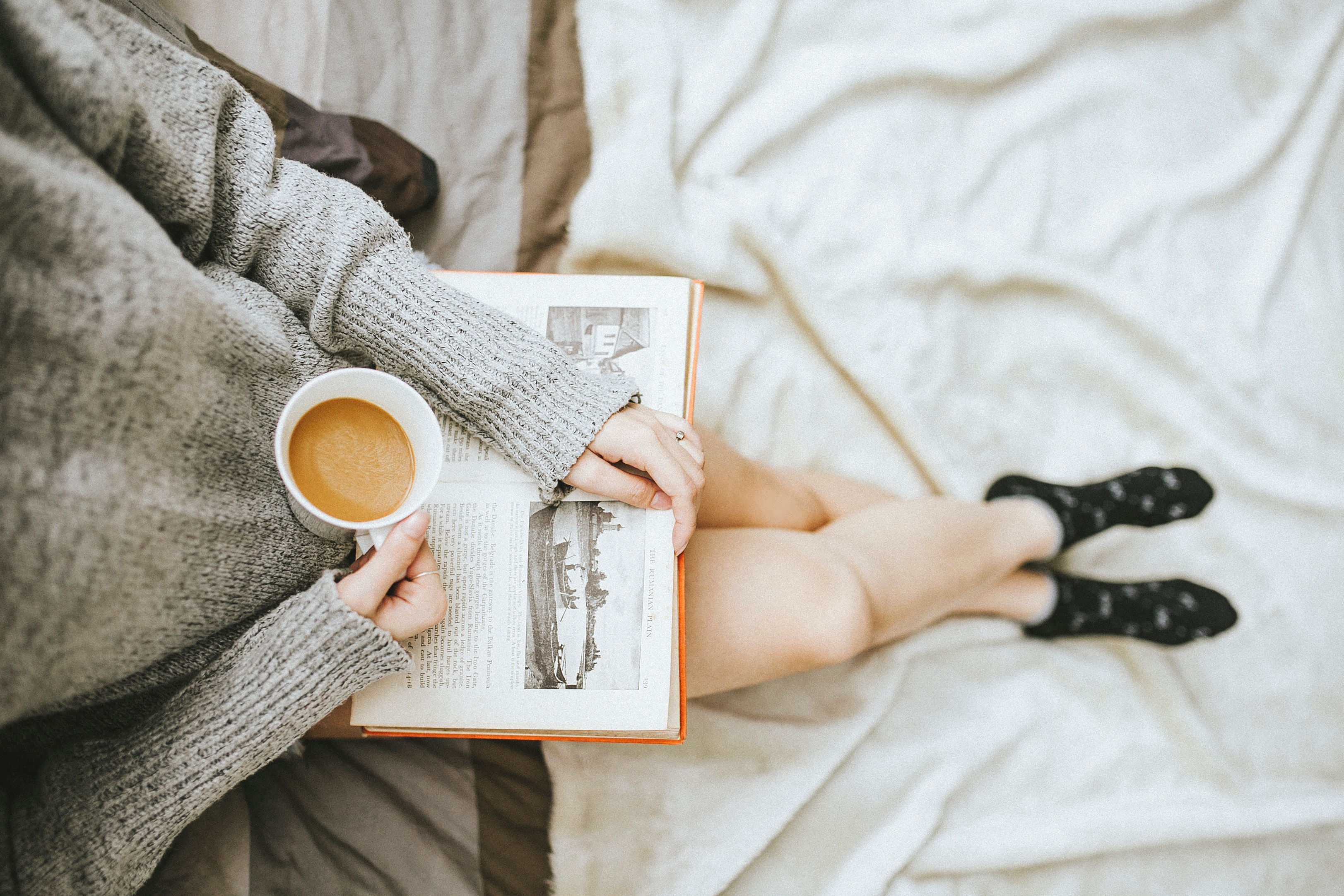 woman holding a coffee mug and reading a book