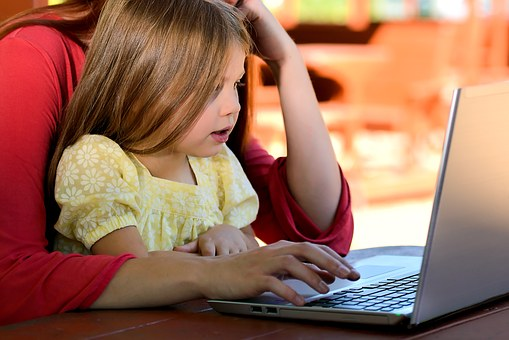 women working with her child on a laptop