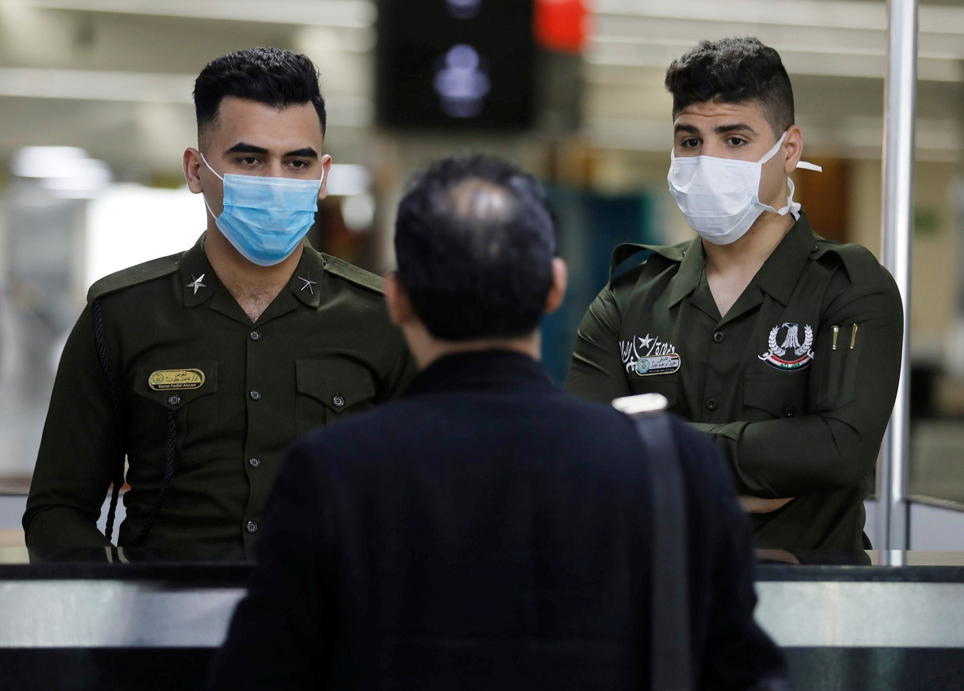Iraqi police officers wearing protective face masks check a passenger's passport upon his arrival, following an outbreak of coronavirus, at Baghdad international Airport, in Baghdad, Iraq March 4, 2020. REUTERS/Khalid al-Mousily