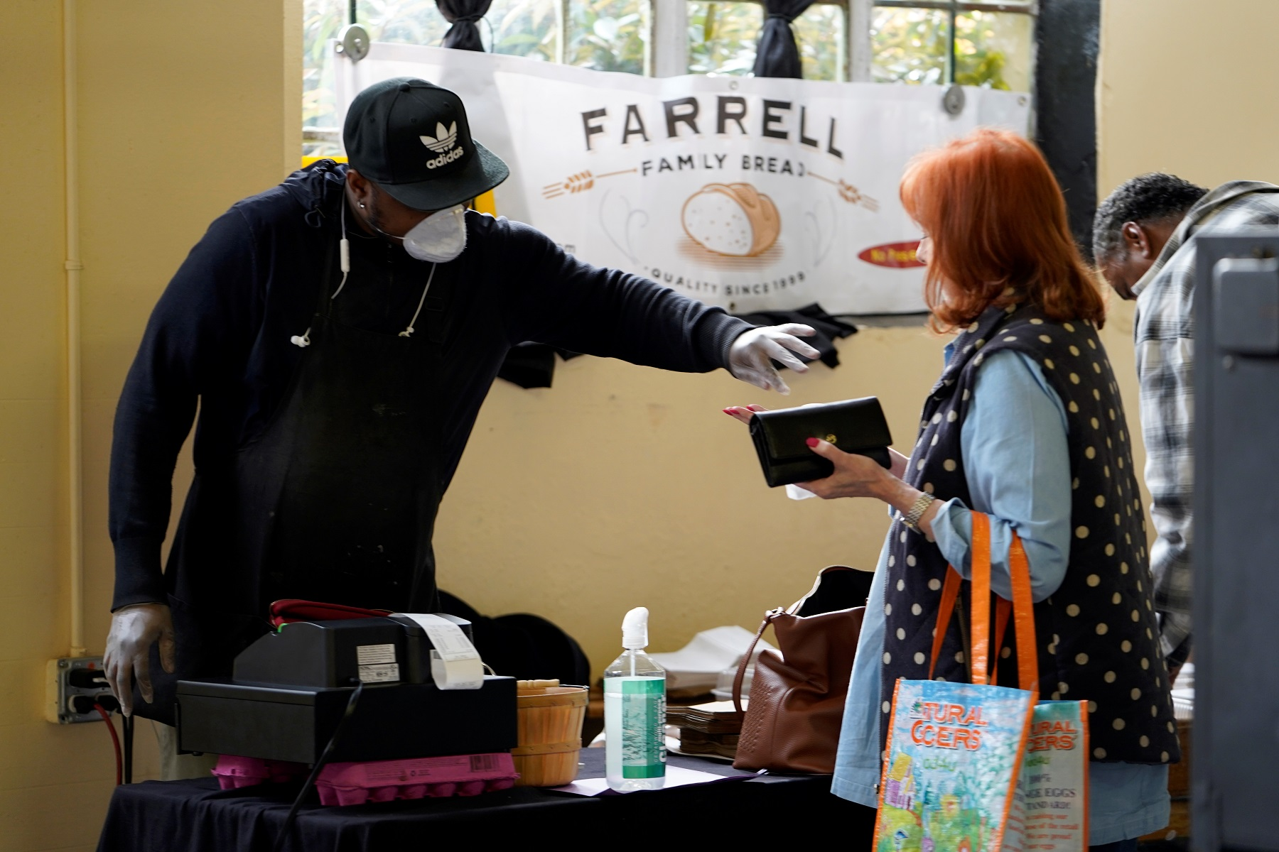 Vendor Cedric McIver gives change back to a customer at the Farmers Public Market in Oklahoma City, Oklahoma, U.S., March 21, 2020. Picture taken March 21, 2020. REUTERS/Nick Oxford