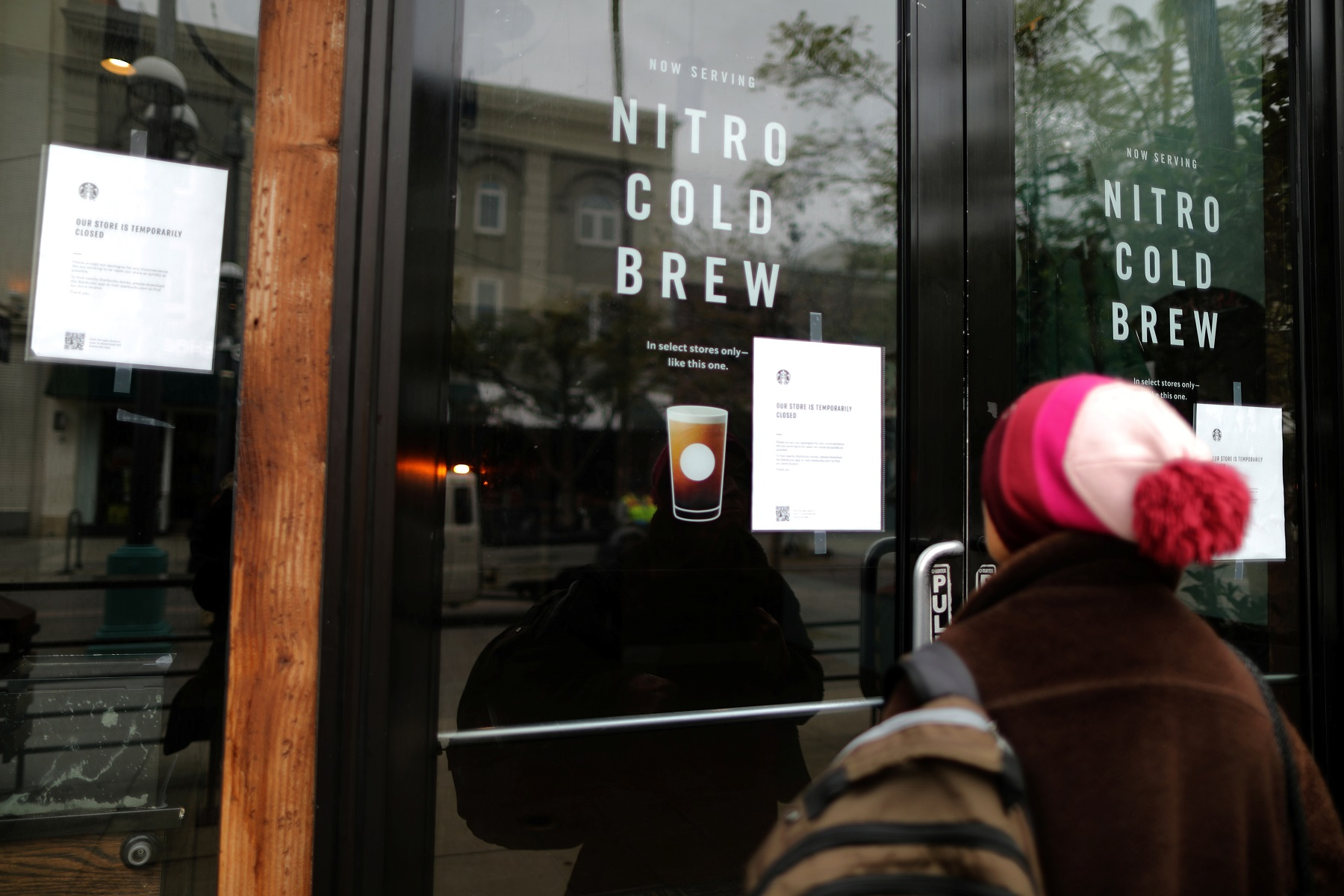 A woman reads a closed sign at Starbucks during the global outbreak of coronavirus (COVID-19) in Santa Monica, California, U.S., March 16, 2020.  REUTERS/Lucy Nicholson