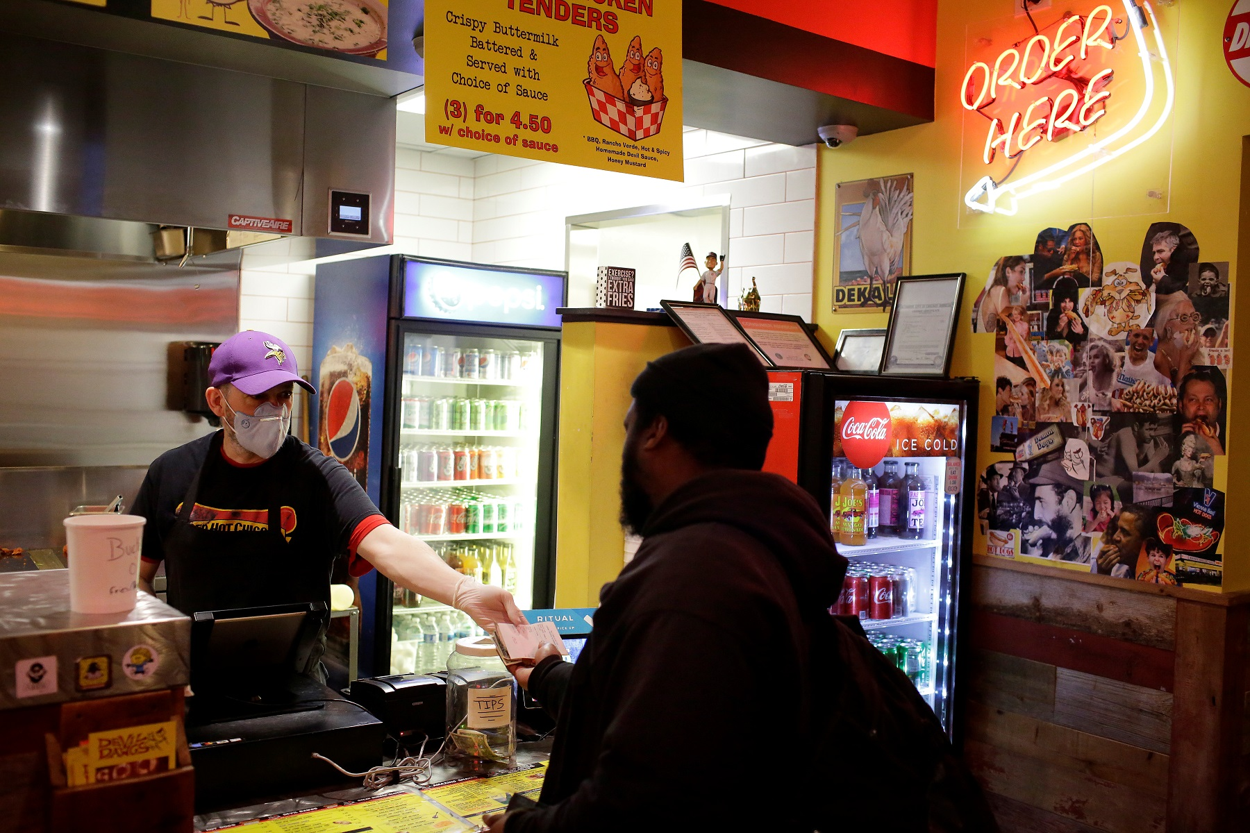 Daniel Thomas takes an order from a customer at Devil Dawgs restaurant as Illinois Governor J.B. Pritzker ordered all restaurants and bars closed at the end of the business day, as part of efforts to combat the spread of novel coronavirus, in Chicago, Illinois, U.S. March 16, 2020. REUTERS/Joshua Lott