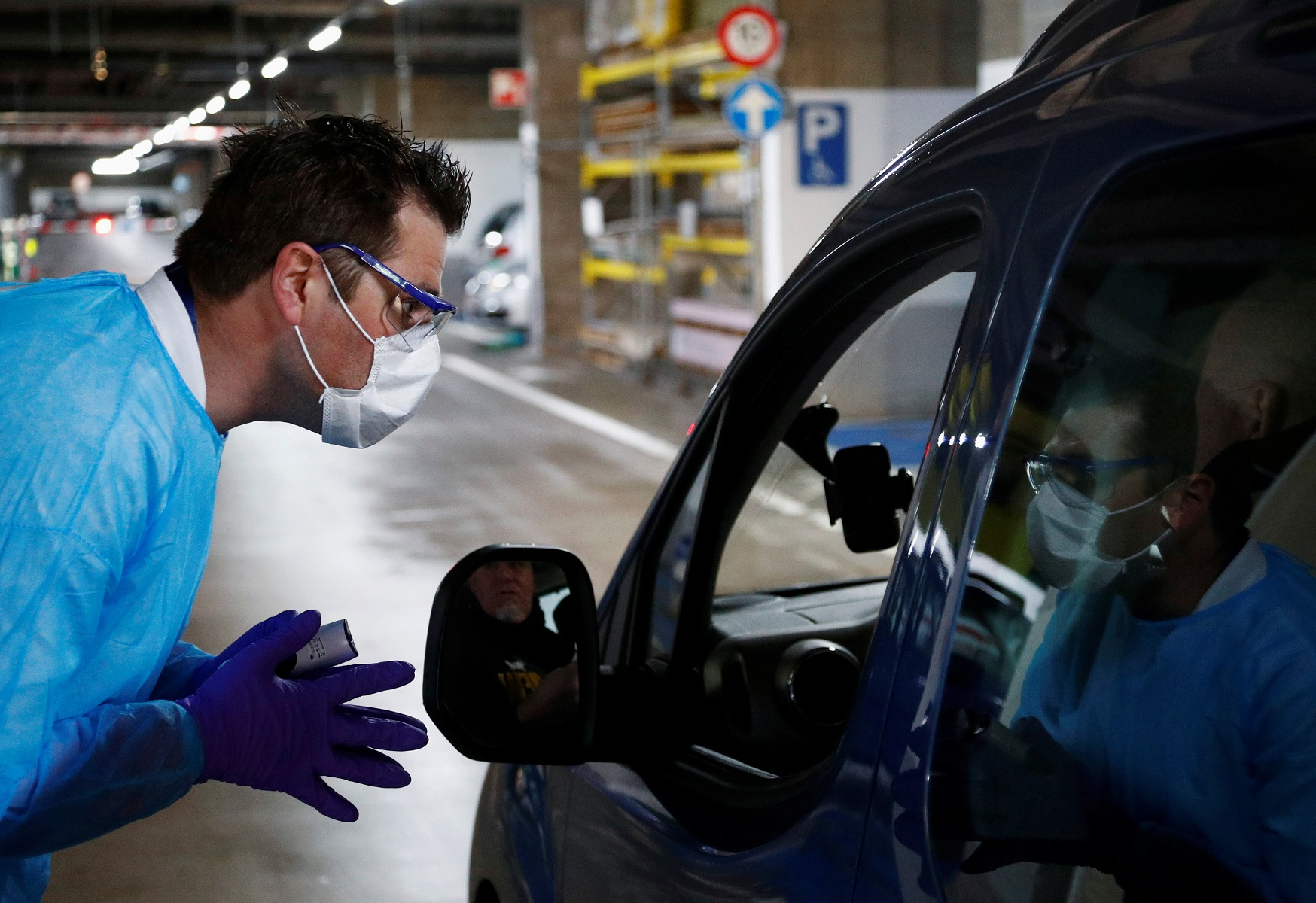 Biologist Jerome De Marchin talks to a patient while he sits in his car at a drive-in testing site for coronavirus (COVID-19) at the Regional Hospital Center in Liege, Belgium March 11, 2020.  REUTERS/Francois Lenoir