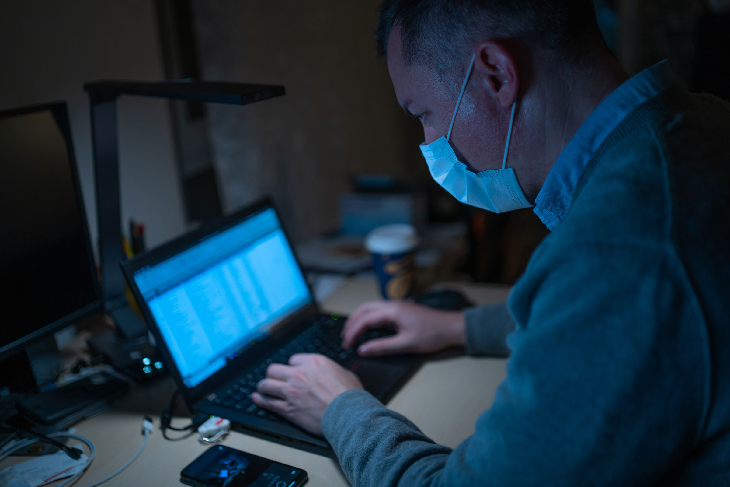 A man in a mask working on a laptop in a dimly lit room