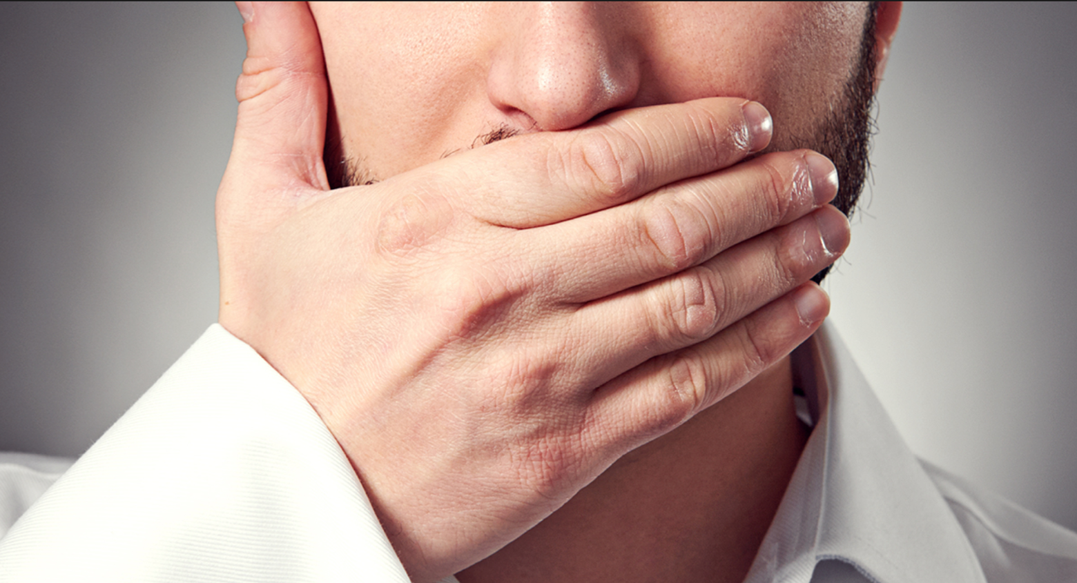 Man is holding a hand in front of his mouth to prevent from talking