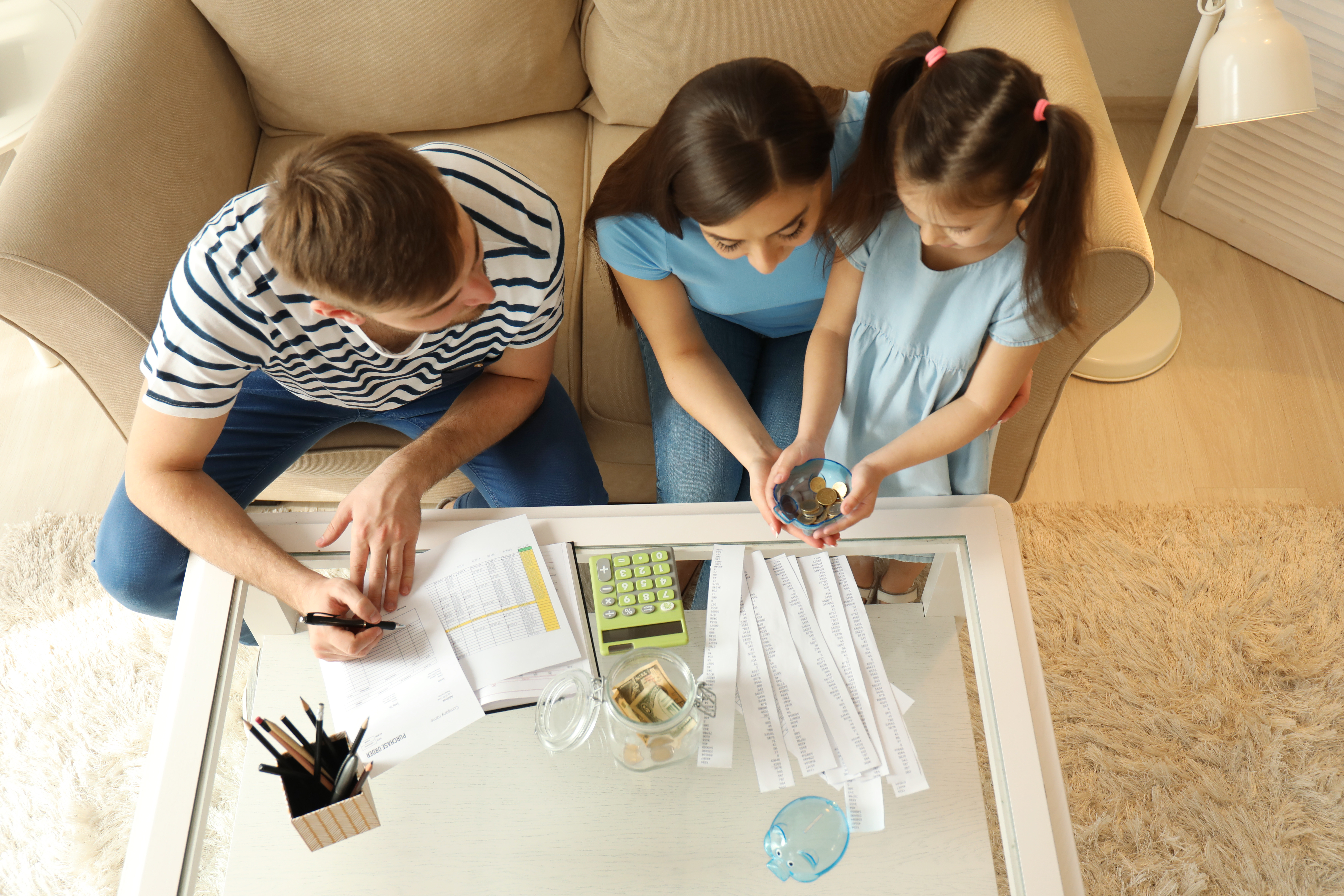Family paying bills together, using a calculator and counting money in living room.